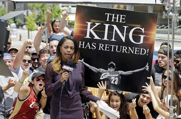 Fans cheer behind an ESPN reporter outside Quicken Loans Arena in Cleveland after NBA superstar LeBron James announced he would return to the Cavaliers on June 11. (Associated Press)