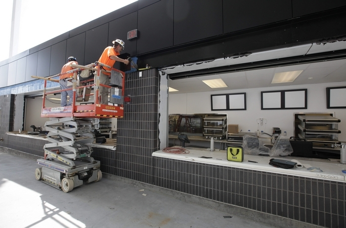 Workers on Monday install trim outside one of four new concession stands on the 300 level at Ralph Wilson Stadium.  (Derek Gee/Buffalo News)