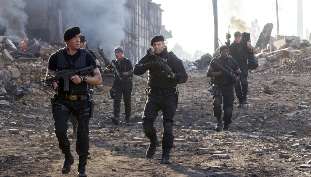 "Sylvester Stallone, left, and Jason Statham, center, on a rescue mission to save the newest members of the group in ""Expendables 3."" (Associated Press)"