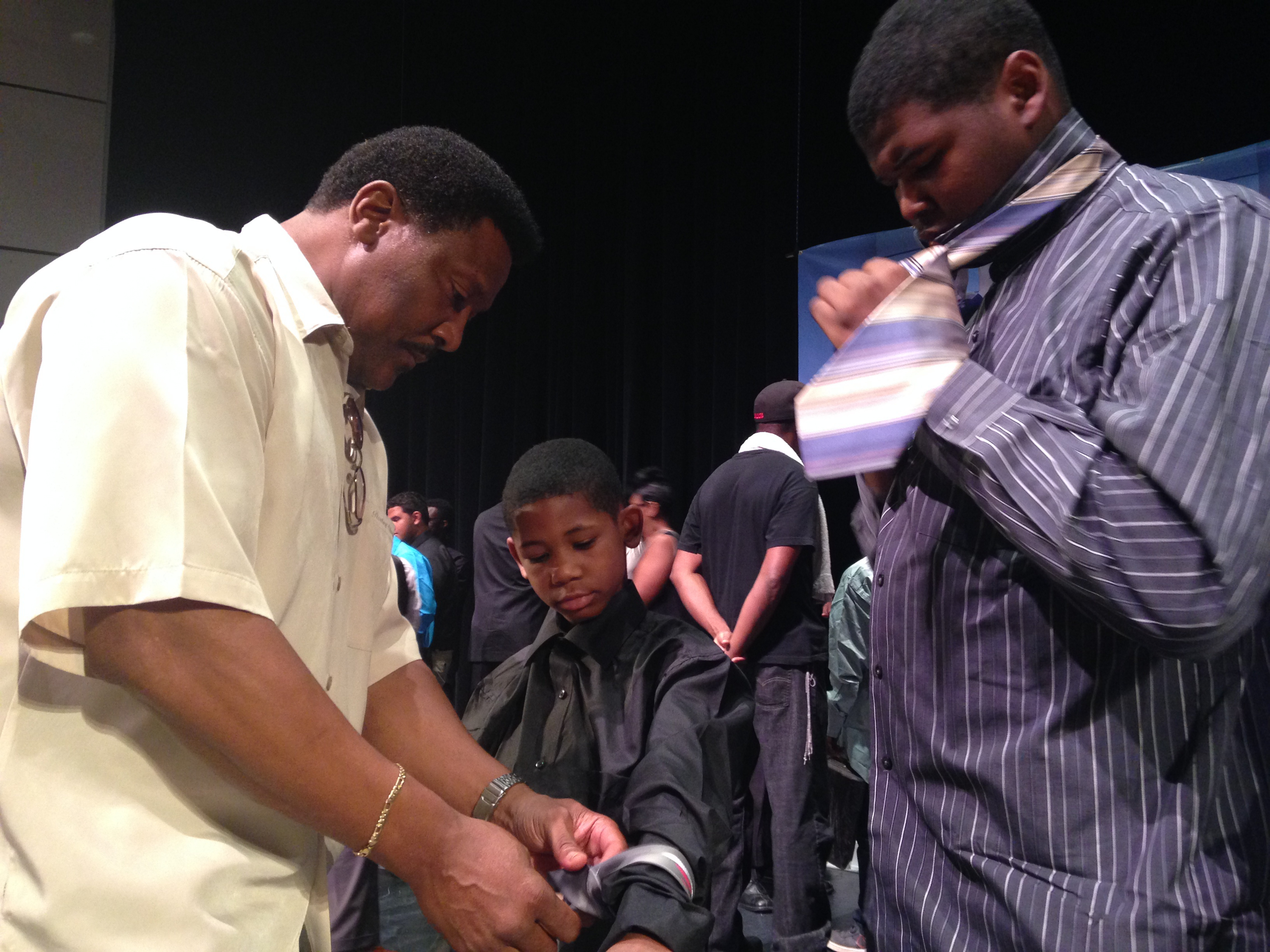 Mentor Douglas Chavers shows brothers Darryl, 8, and Kahlil Emerson, 13, how to tie their ties Saturday at the Boys to Men conference.