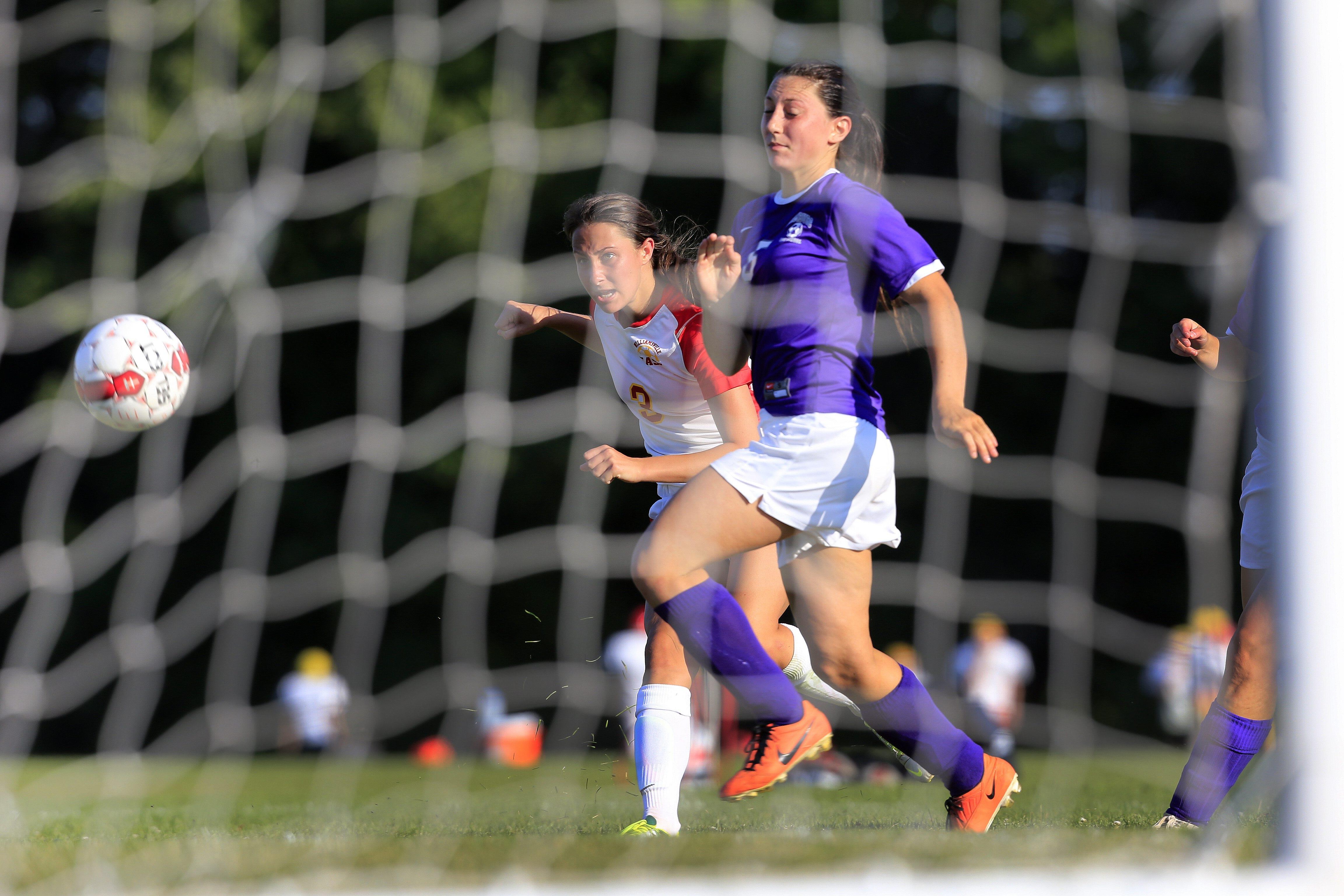 Williamsville East's Marissa Birzon shoots past Hamburg's Katie Villarini in Thursday's game. Birzon scored all four East goals.