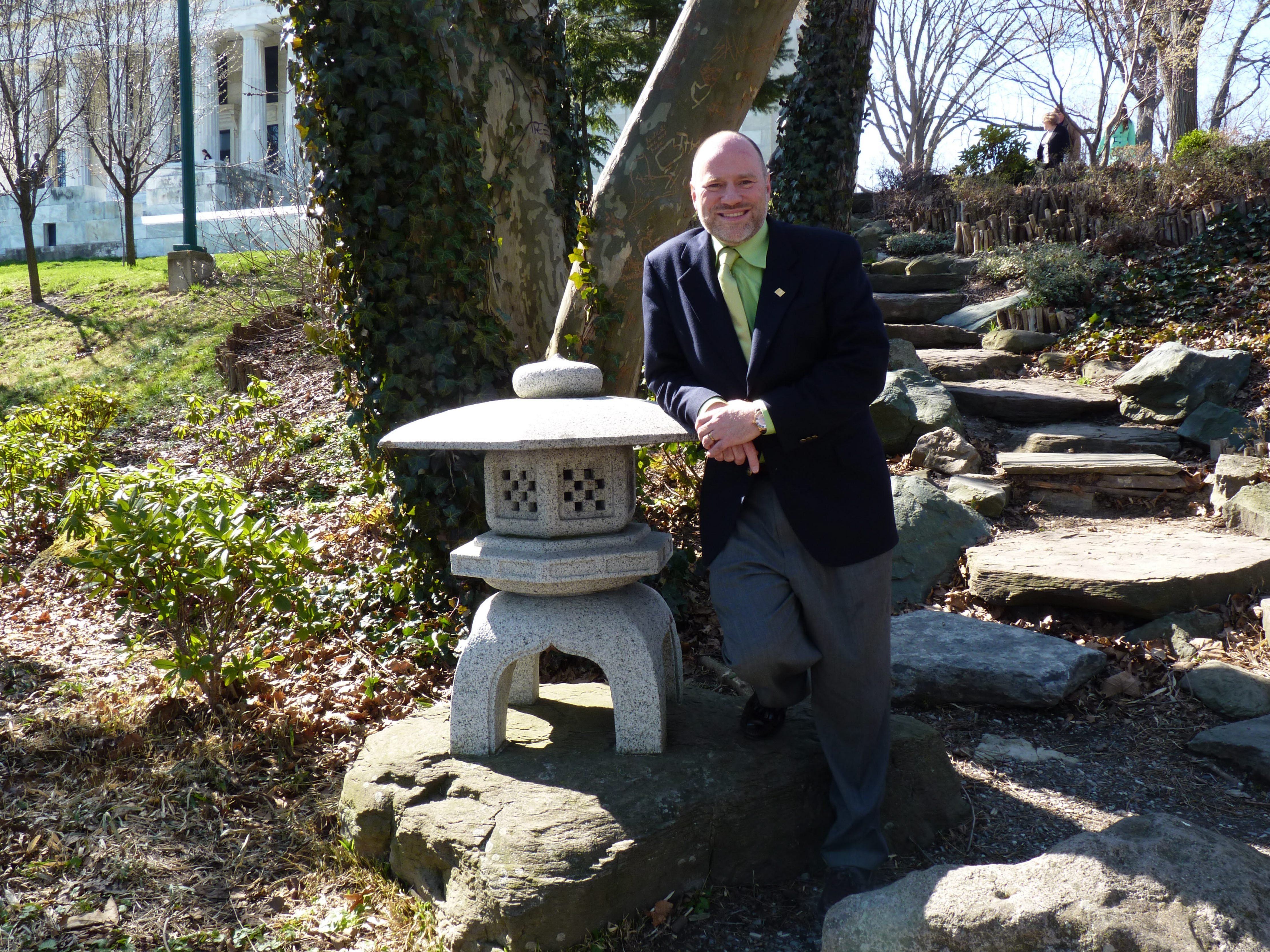Thomas Herrera-Mishler posed last year with one of three stone lanterns that define the Japanese Garden in Delaware Park.