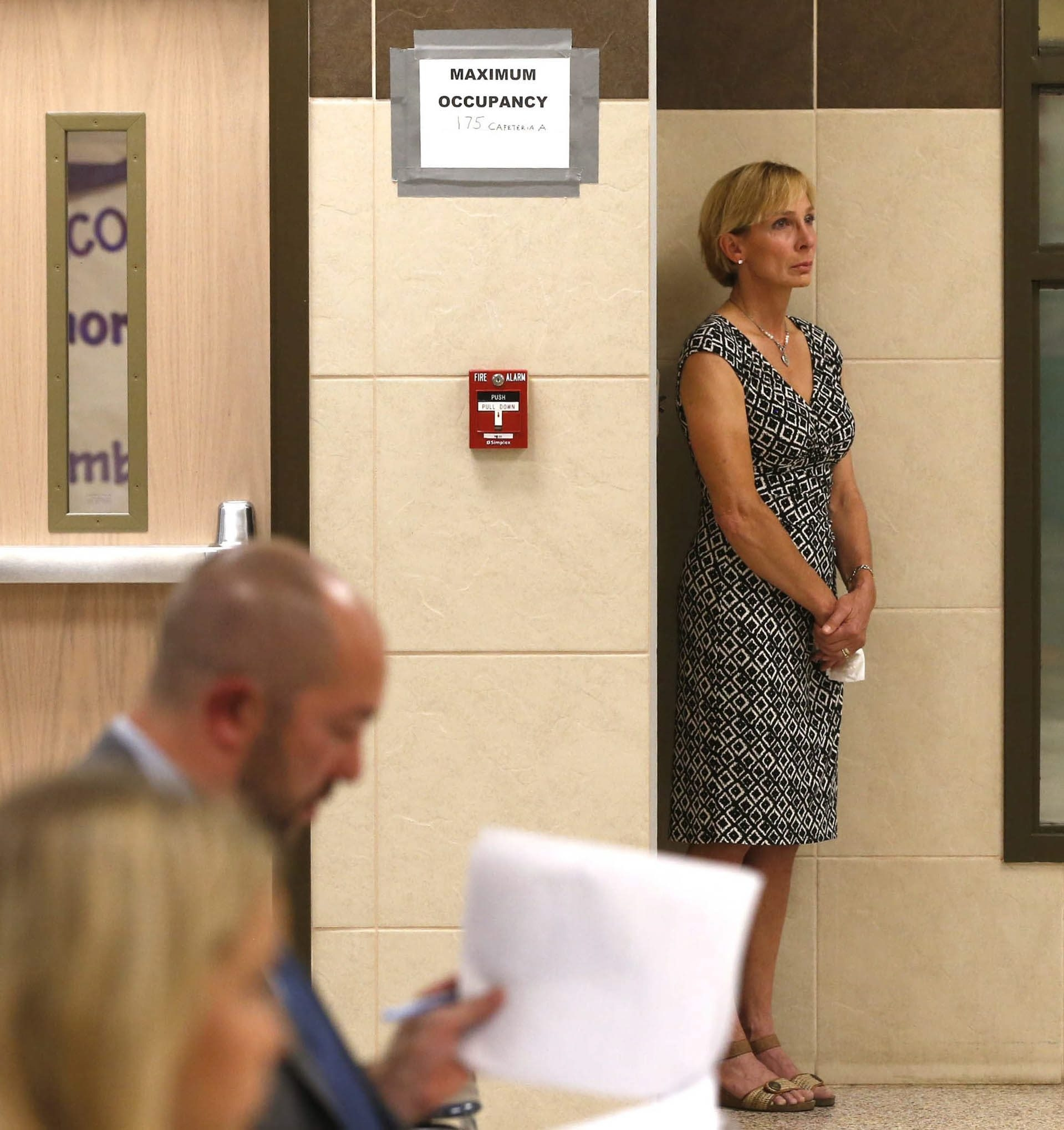 Catherine Schrauth Forcucci stands aside to collect her thoughts while misconduct charges are read during the final hearing that led to her removal from the Hamburg School Board.
