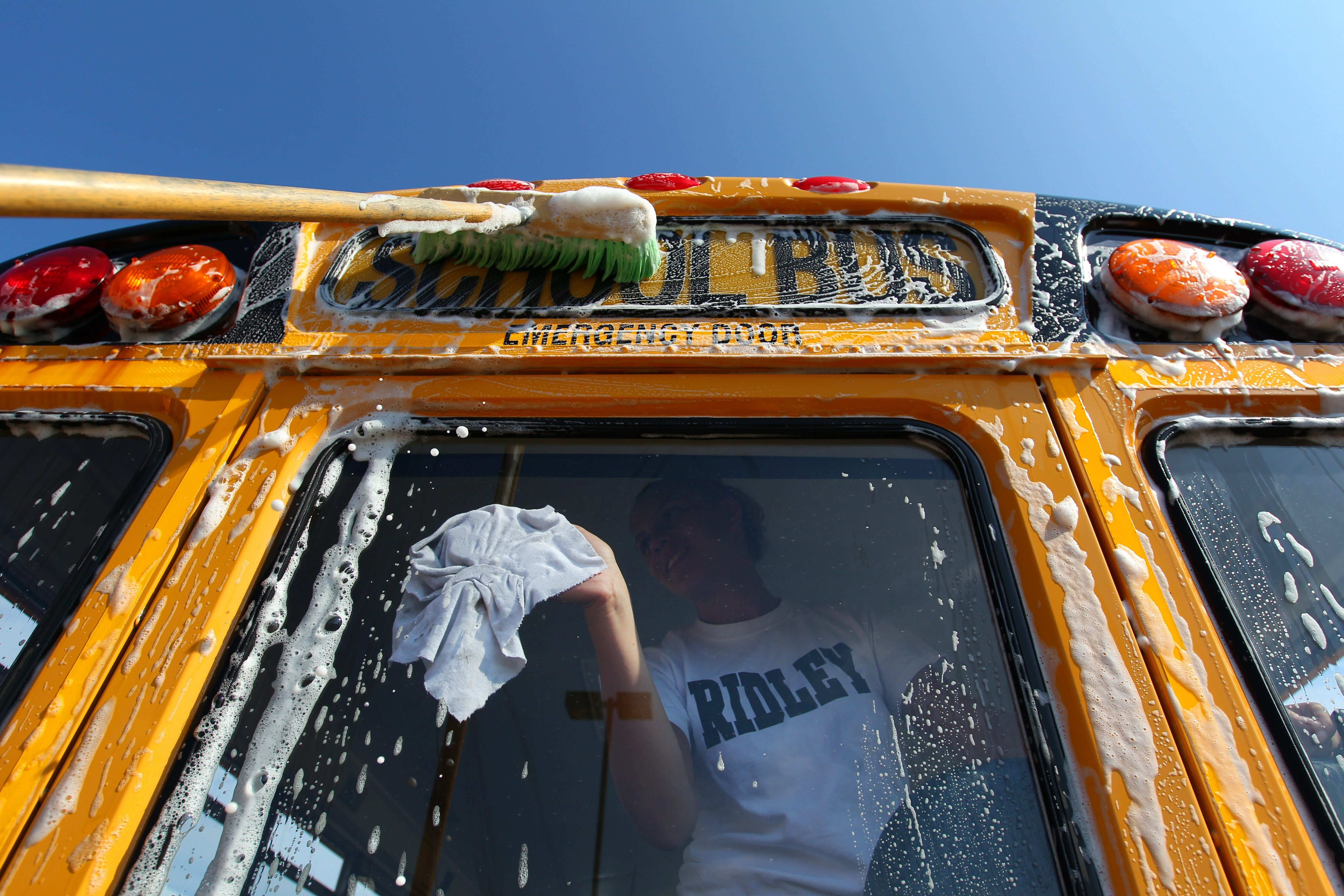 """It's pretty much the best summer job you can ask for,"" says Sydney Glynn, who washes a window on a West Seneca Central School District bus last month.  See a photo gallery at BuffaloNews.com."