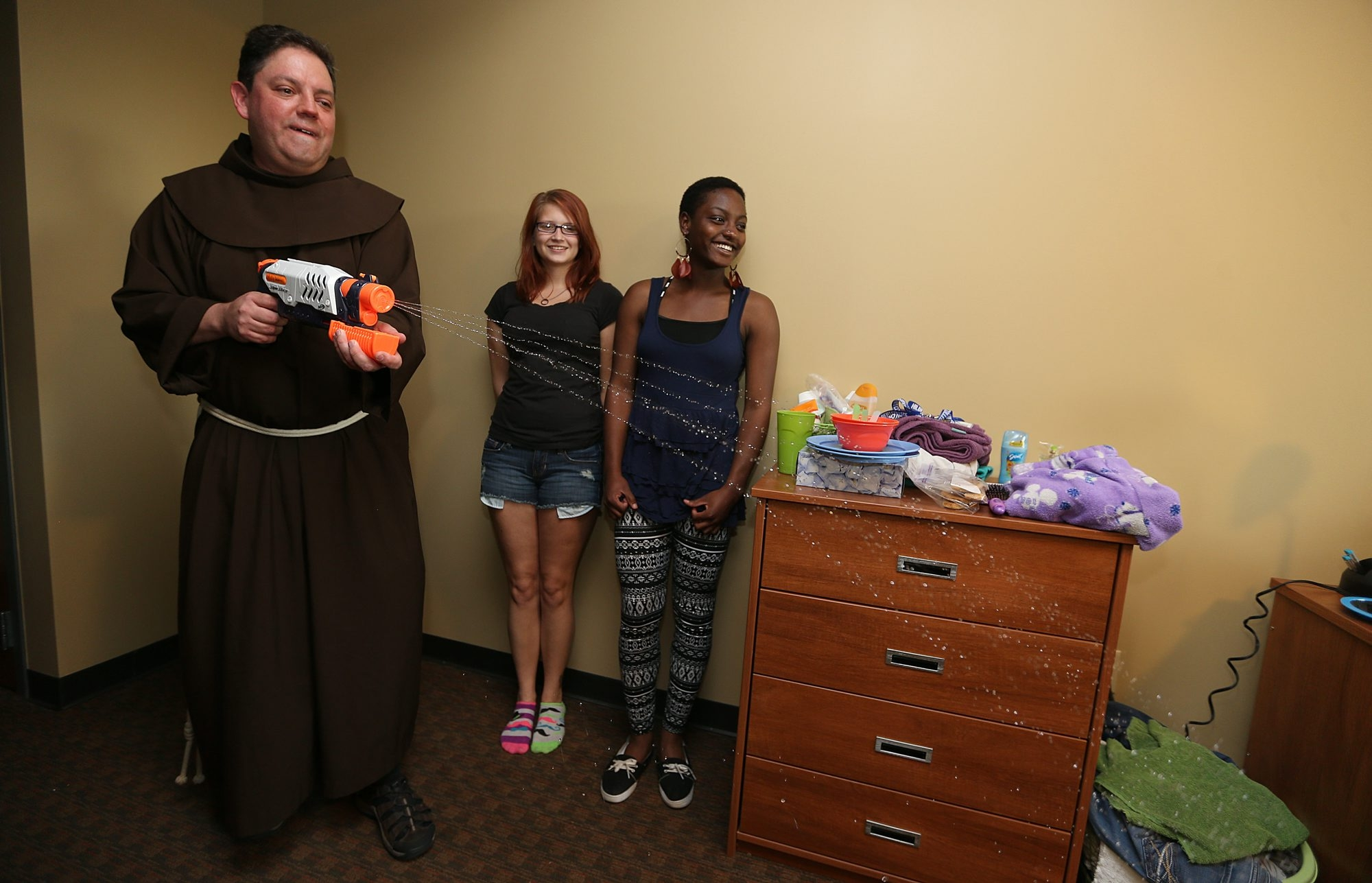Father Greg Jakubowicz blesses the dorm room of Jennifer Williams, left, and Tatyona Duke with holy water from a  water gun  at Hilbert College in Hamburg Wednesday.