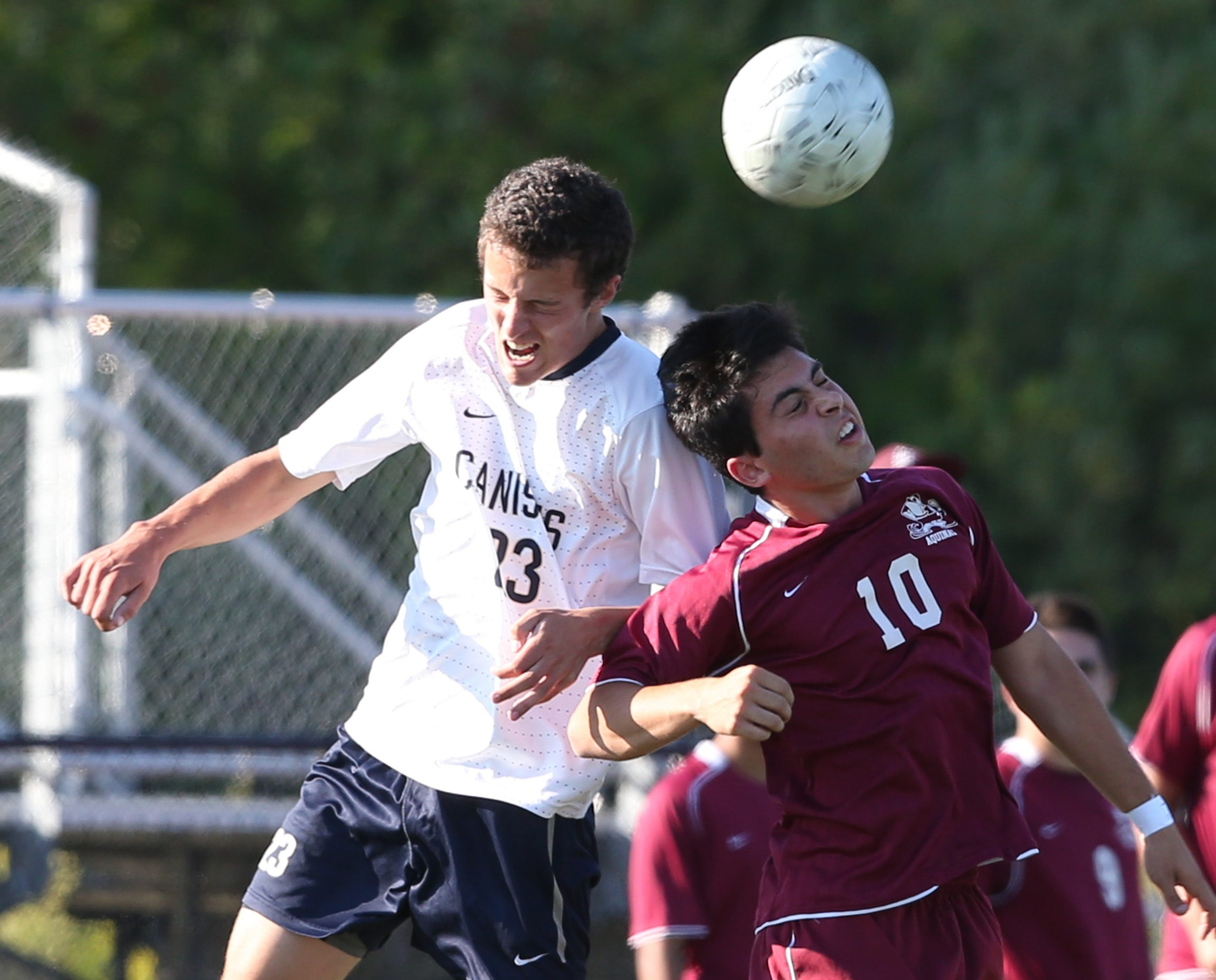 Canisius'  Matthew Burns heads a ball away from Aquinas'  Mike Fuino during the Crusaders' season-opening win over the Rochester-area power.