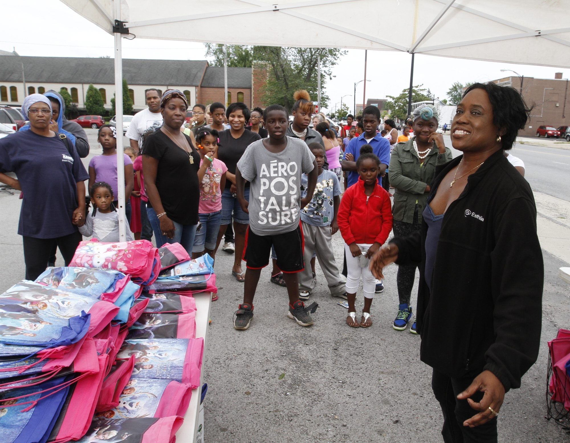 Lines gather Tuesday as backpacks filled with school supplies are donated to Buffalo school children in a program called Backpack Splash, coordinated by Esthlia Hunt , right, at  Kensington and Bailey Avenues in Buffalo.