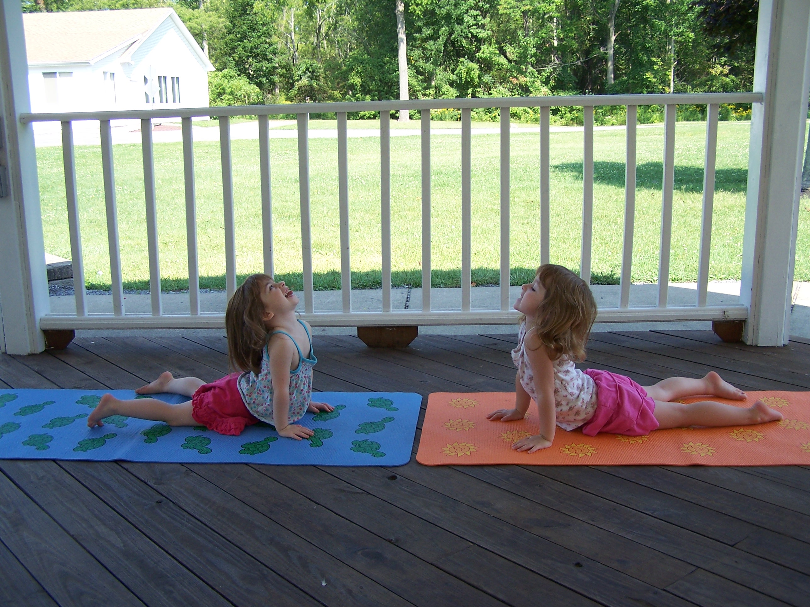 Iris Leatherbarrow, left, and her sister, Mica, pictured in the cobra yoga pose, often help their mother, Julie, teach her Budding Tree Yoga classes. (Julie Leatherbarrow)