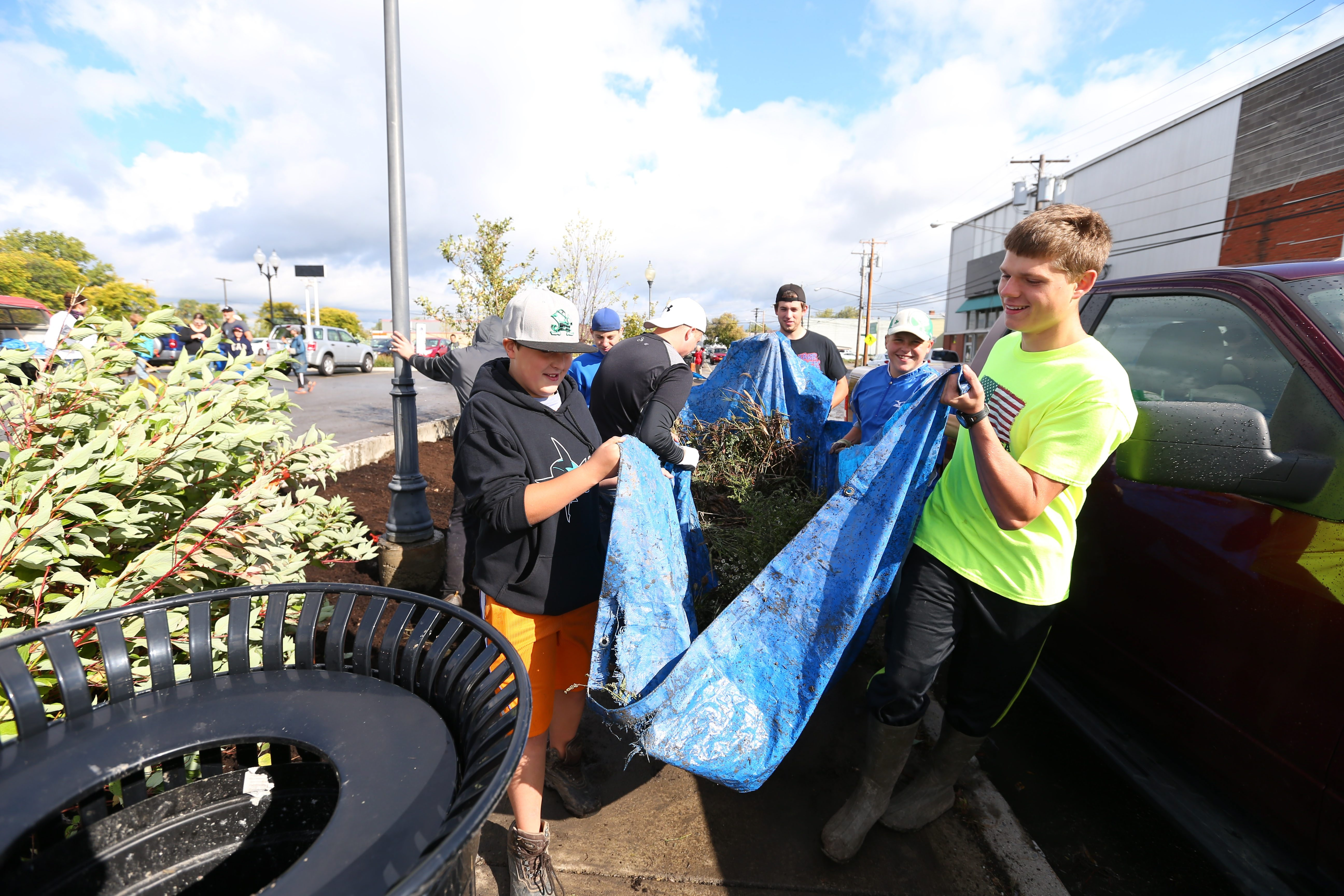 Eagle Scout candidate Nick Kaszynski, right, and friends carry a tarp full of weeds they pulled from flower beds at the Manhattan Street municipal parking lot Saturday in North Tonawanda.