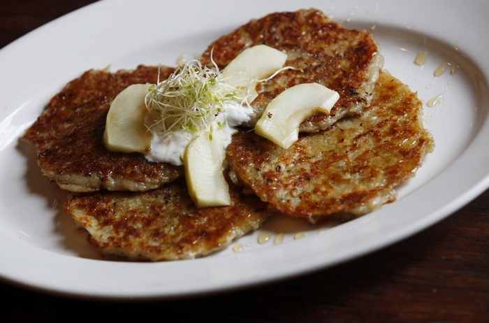 These traditional style potato pancakes, served with green onion, a dollop of sour cream and apple sauce are a favorite in Ulrich's. (Sharon Cantillon/Buffalo News)