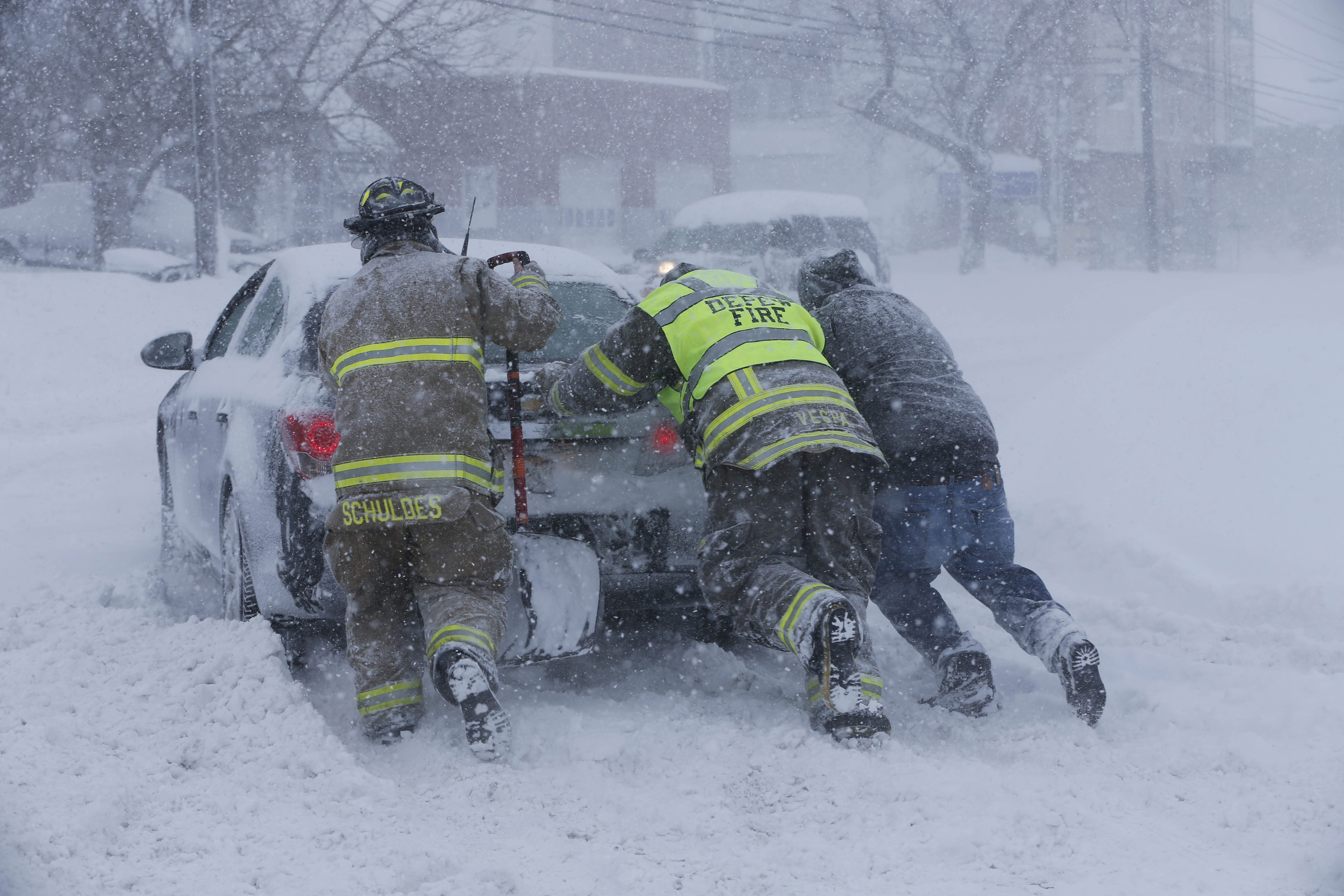 Firefighters from West End Hose Company in Depew help a stuck motorist on Transit Road near George Urban Boulevard, Tuesday.  (Derek Gee/Buffalo News)