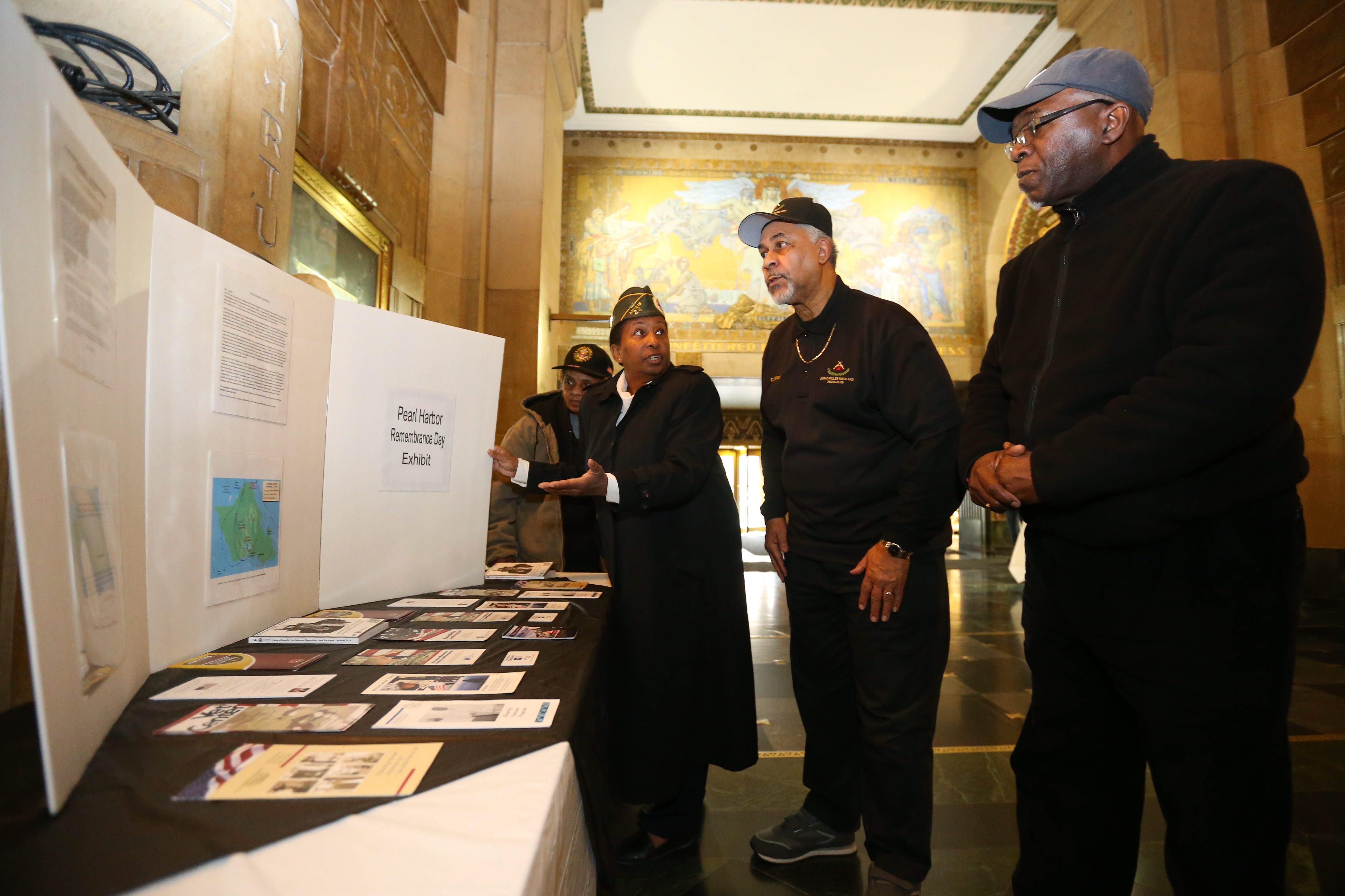 From left, Veronica Johnson, Debbera Ransom, Cary Dixon and Lawrence Strother look over their Pearl Habor exhibit at City Hall in Buffalo on Friday.