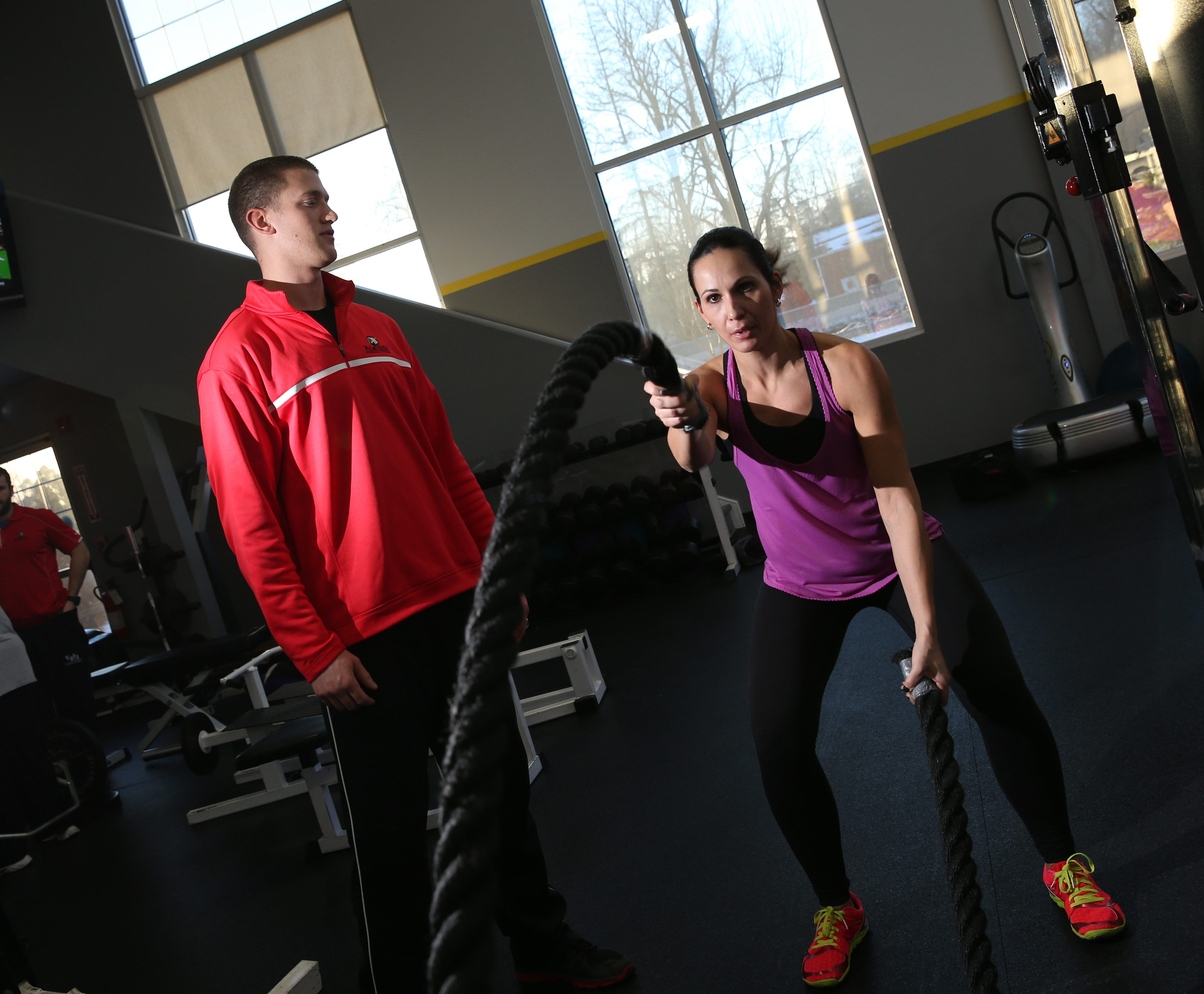 Dianne Myers, 35, of Clarence, is trying to take her fitness to the next level. She works out at Alessi Personal Fitness, Wednesday, Jan. 28, 2015.   She's doing the battle ropes as her trainer Travis Denman works with her.  (Sharon Cantillon/Buffalo News)