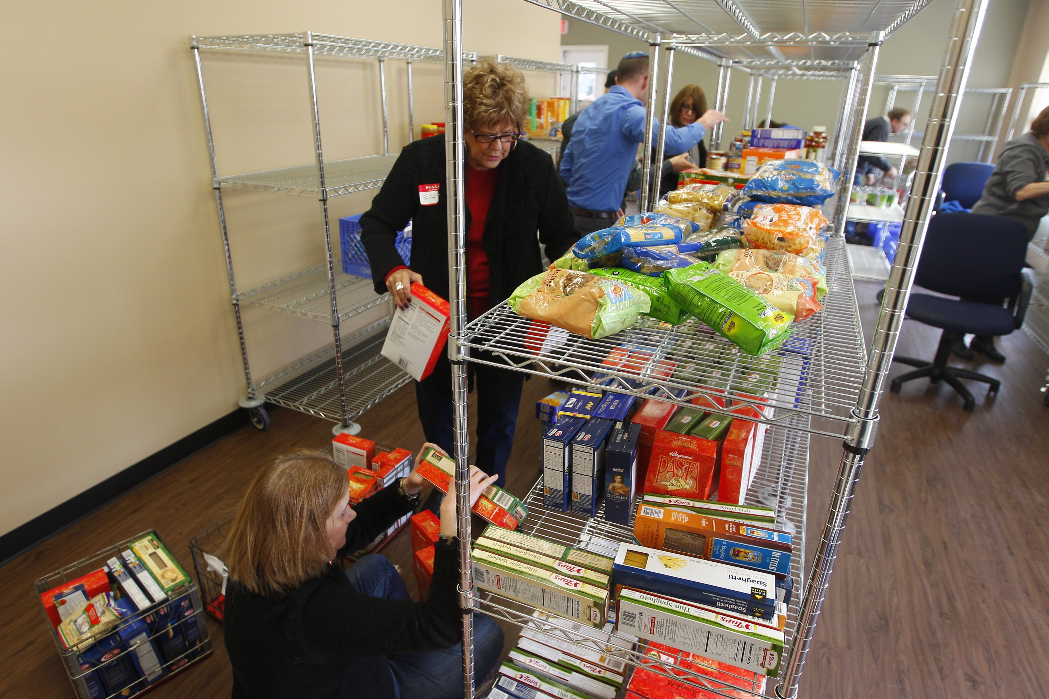 "Volunteers stock shelves with first food donations at Town Square for Aging on the Weinberg Campus, a collaborative effort by Catholic and Jewish groups whose staff is ""going to be busy."""