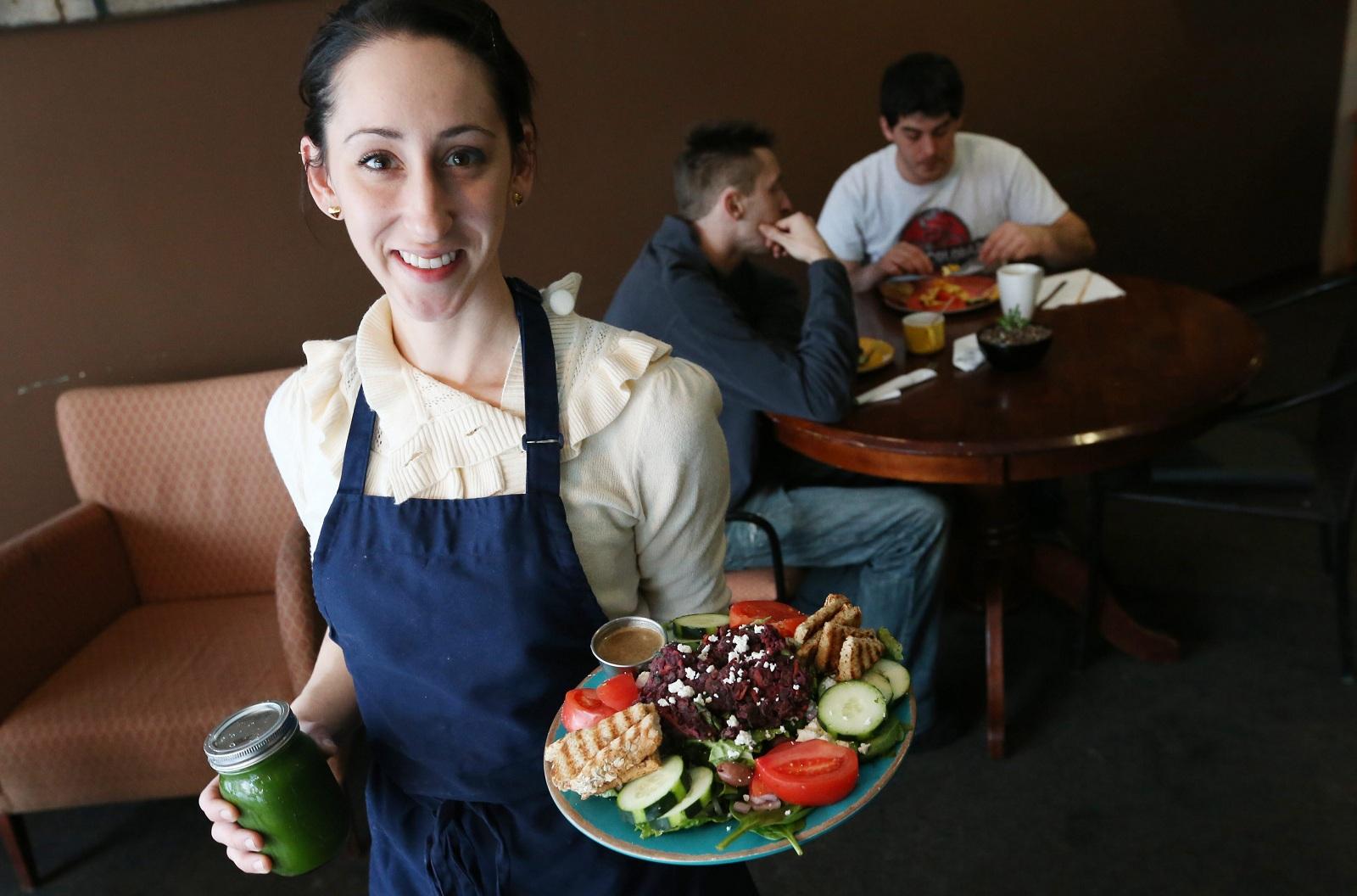 Ashker's co-owner Sarah Nasca presents the black bean veggie burger salad. (Sharon Cantillon/Buffalo News)