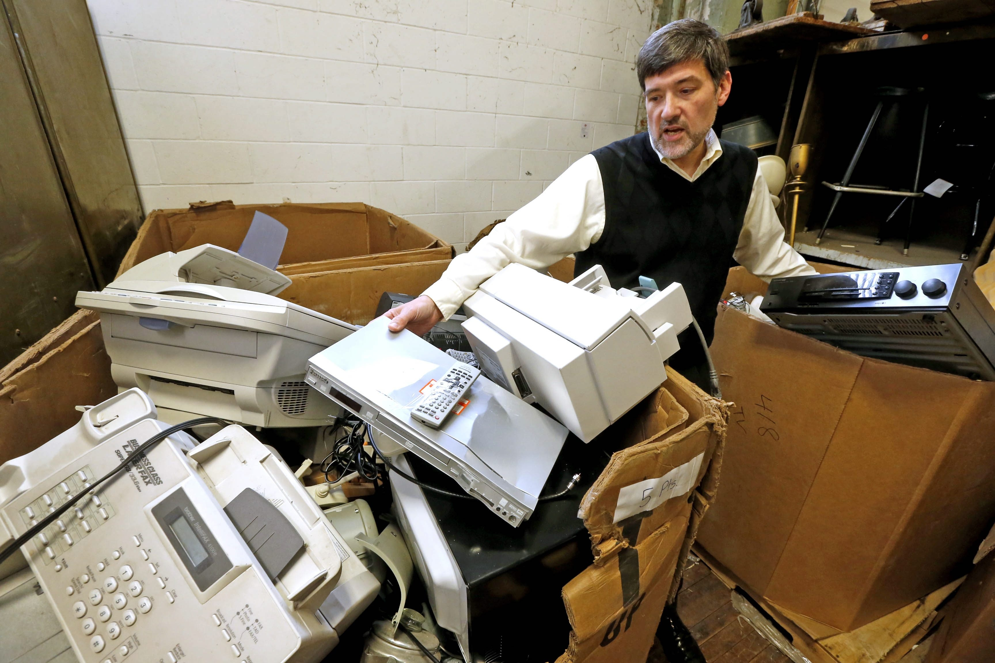 Director Mark Zirnheld places a DVD player in a carton filled with electronic devices that people have donated to the St. Vincent de Paul Society.