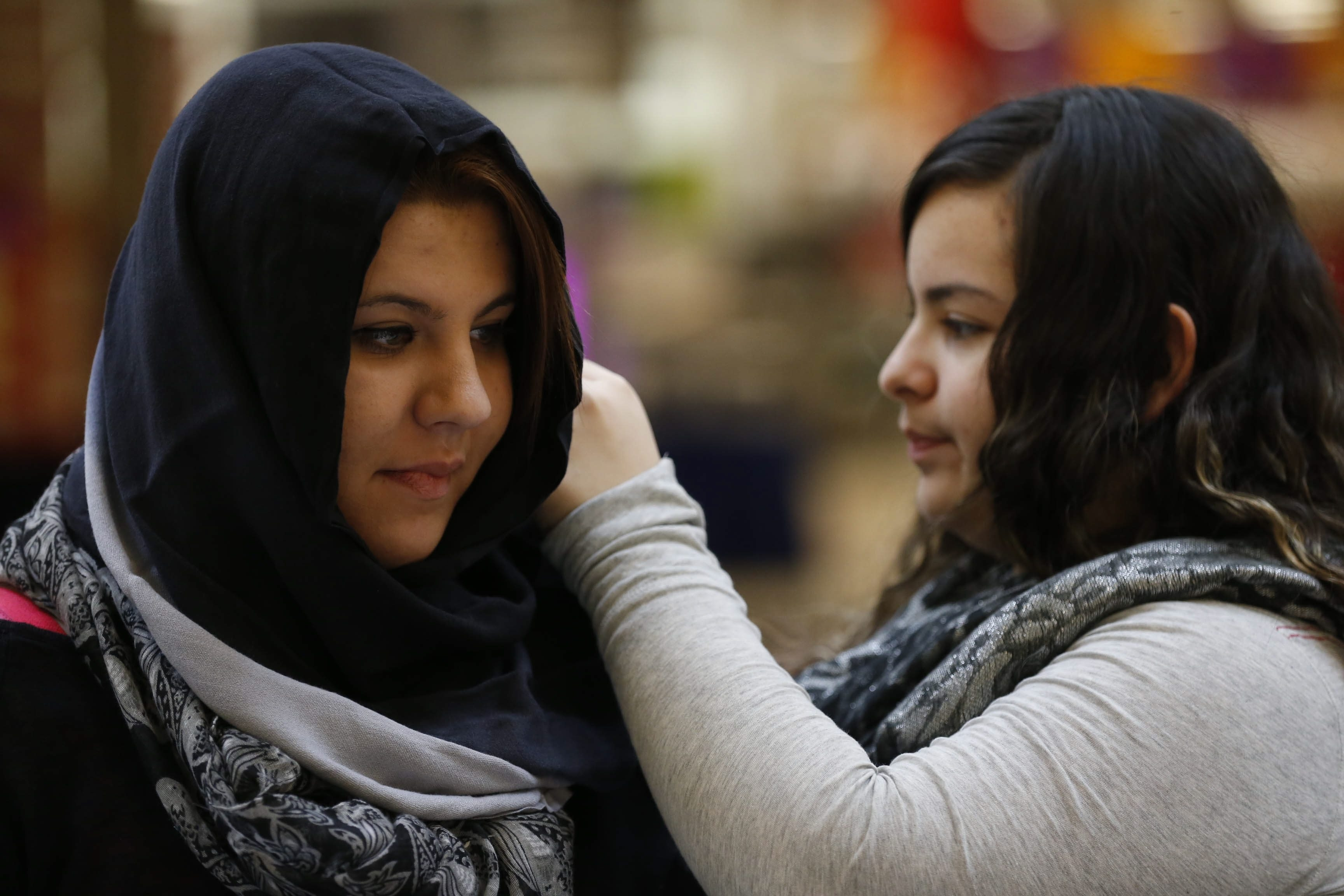 """Marijka Walters, left, lets Alexandria Rodriguez, who is not Muslim, adjust her hijab during an informational appearance at the Walden Galleria to celebrate World Hijab Day on Sunday. Hijab is a veil or scarf that means """"cover"""" in Arabic.  """"The reason that I wear it is that it's a commandment of Allah, that women be modest."""" –Rose Salley of Buffalo, who converted to Islam in 2011."""