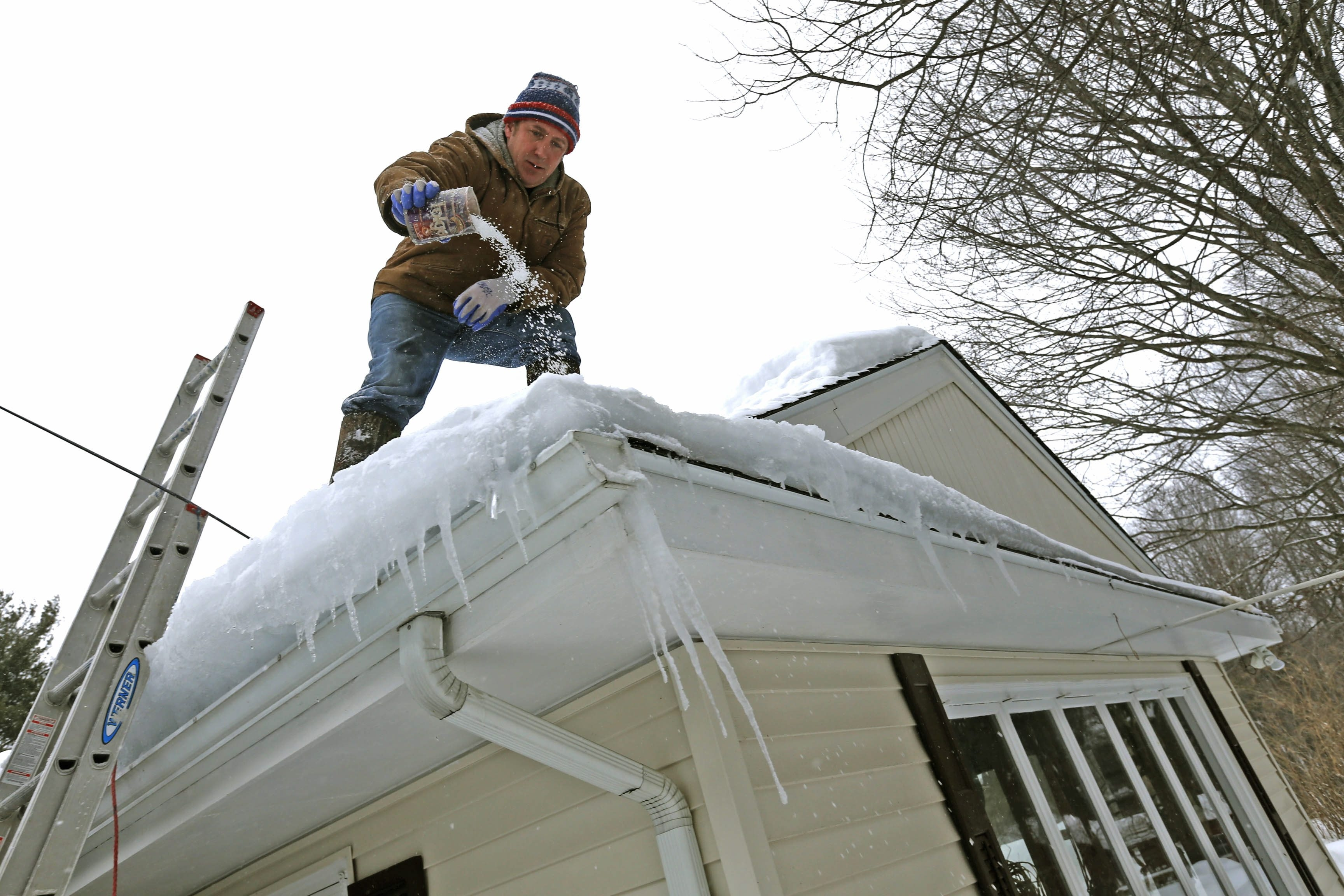 Armed Tuesday with a shovel and pail of granulated ice-melting compound, Geoff Gunner takes to the roof of a family member's home on Girdle Road in Elma, hoping to reduce the build-up of ice dams that threaten the home.