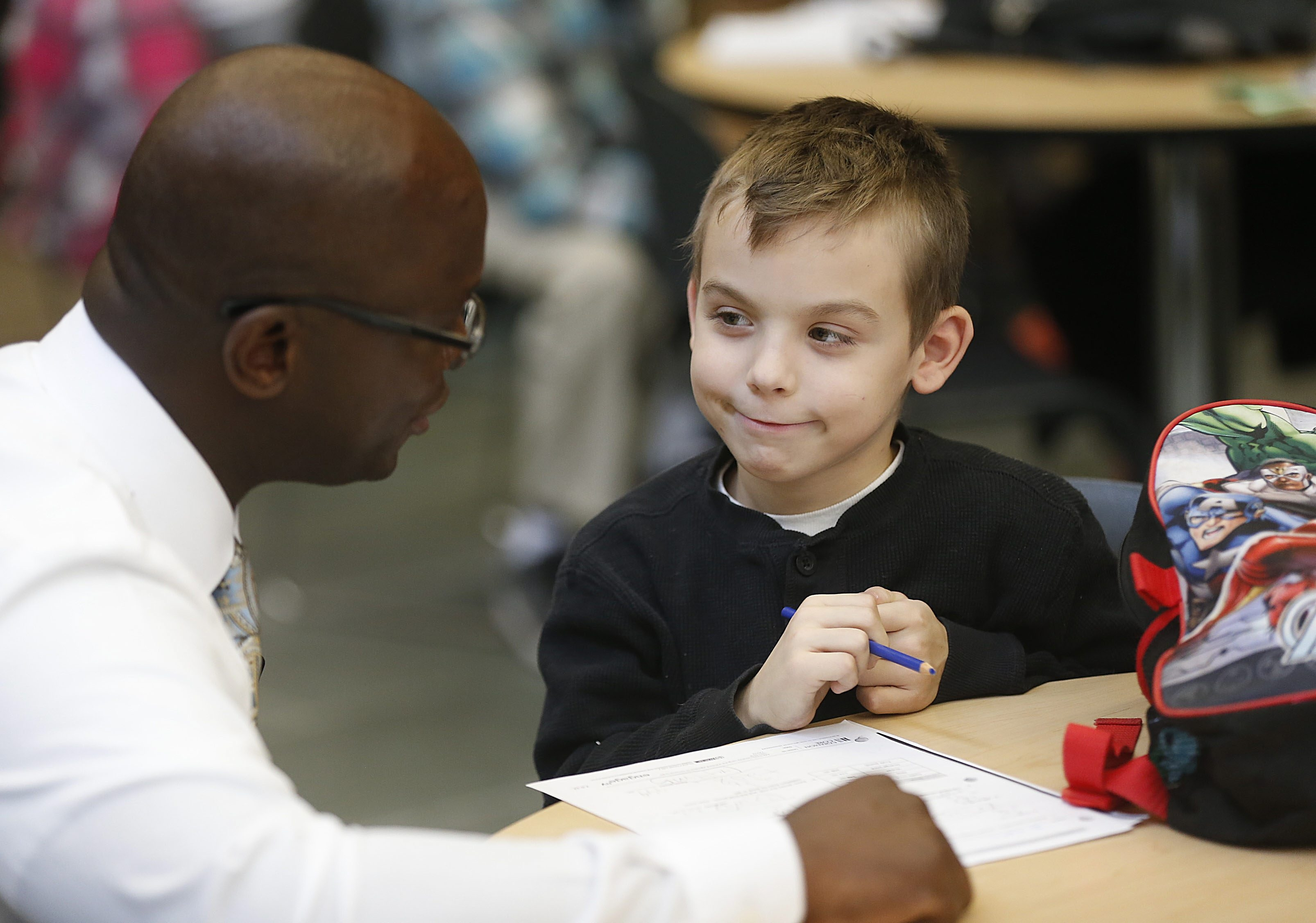 Principal Gregory Mott visits with third-grade student Steven Stroh, 8, during an after-school program at William J. Grabiarz School of Excellence. The school saw some of the district's biggest gains on state tests.