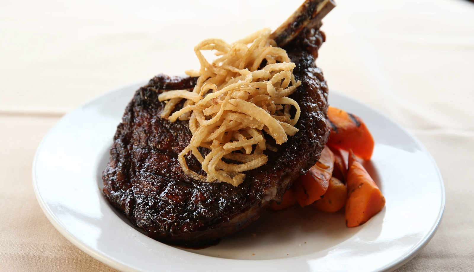 Molasses glazed and grilled cowboy steak, which is a 24-ounce, bone-in ribeye, served with potato croquettes, grilled broccoli, carrots and crispy shoestring onions. (Sharon Cantillon/Buffalo News file photo)