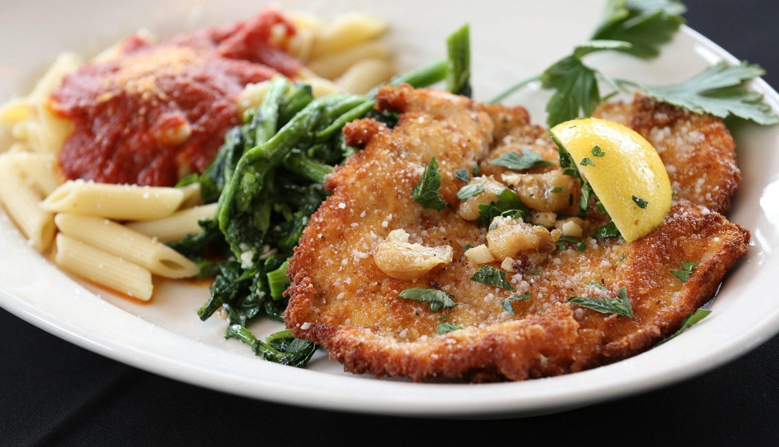 Chicken with lemon, garlic and caper garnish accompanied by rapini greens and pasta. (Sharon Cantillon/Buffalo News)
