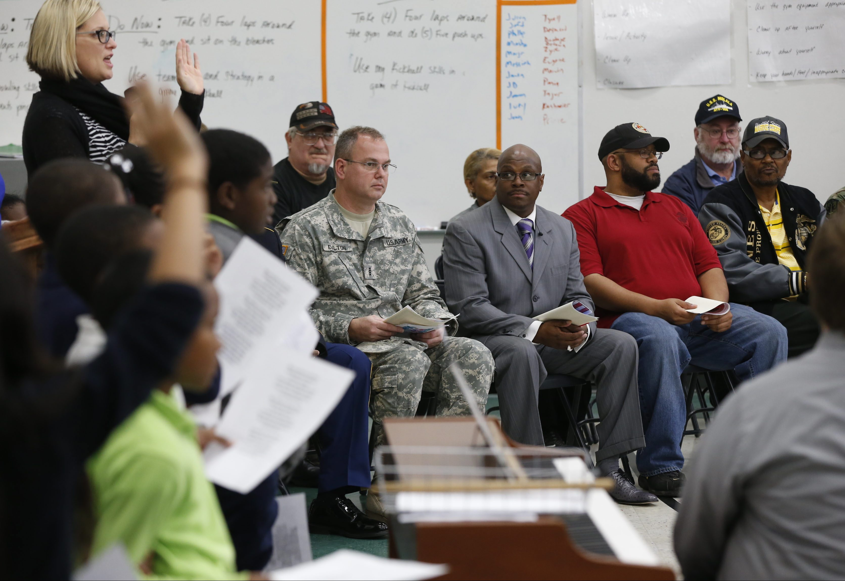 Veterans sit in the front row that were honored.  From left, Scott Dalton, Army, Howard Patton III, Army, Shawn Dukes, Marines, Waverly Jones, Marines on Monday, Nov. 10, 2014.  Buffalo United Charter hosted a 'bring a vet to school' event.  Vets visited  classrooms and then were honored at a school assembly at 1:30 and refreshments.   (Robert Kirkham/Buffalo News)