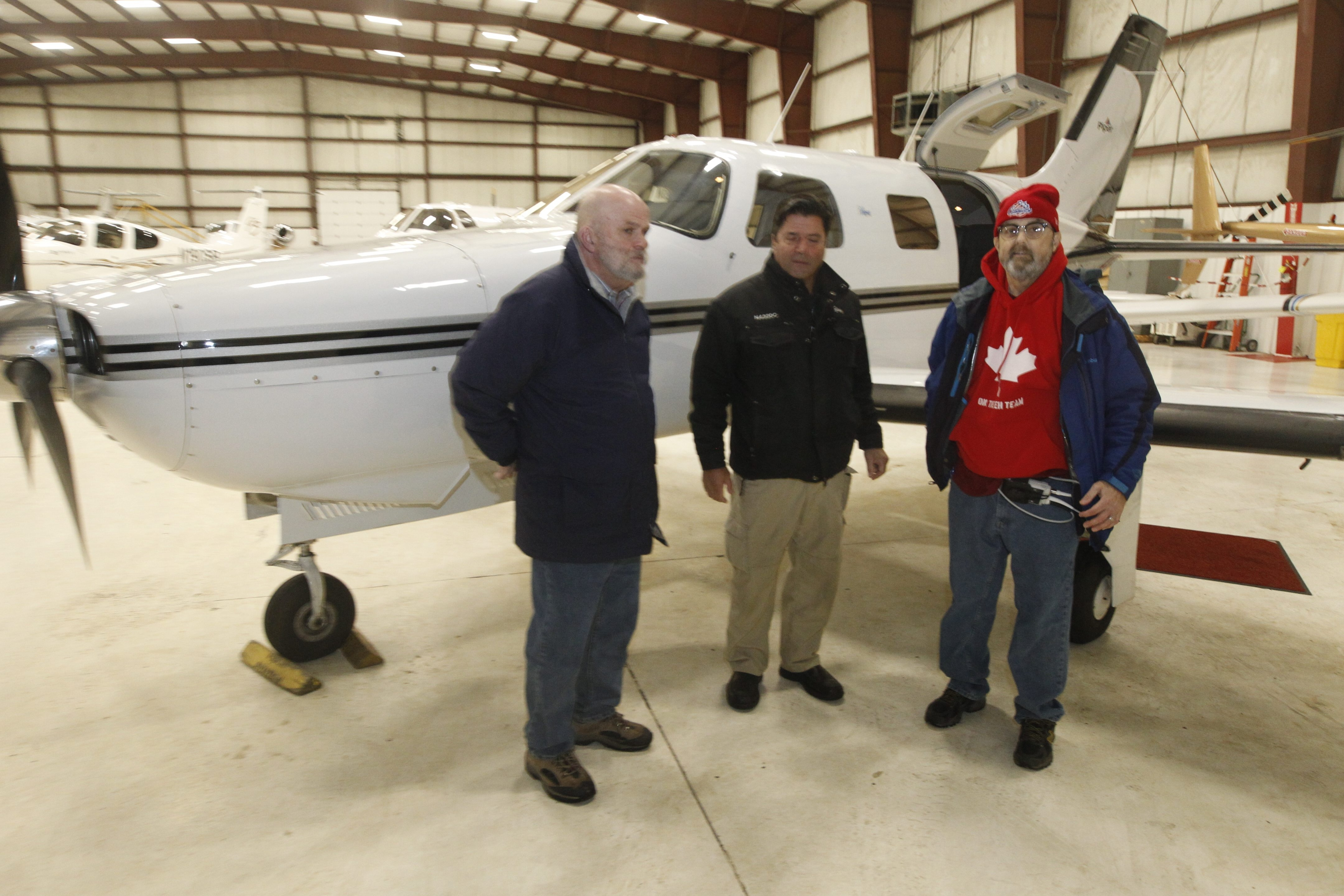 Tim Day, right, a Town of Tonawanda police officer, poses with Joseph DeMarco, Wings Flights of Hope founder, center, and his brother Michael as they prepare to board a plane at Prior Aviation for a flight to Boston and Massachusetts General Hospital.