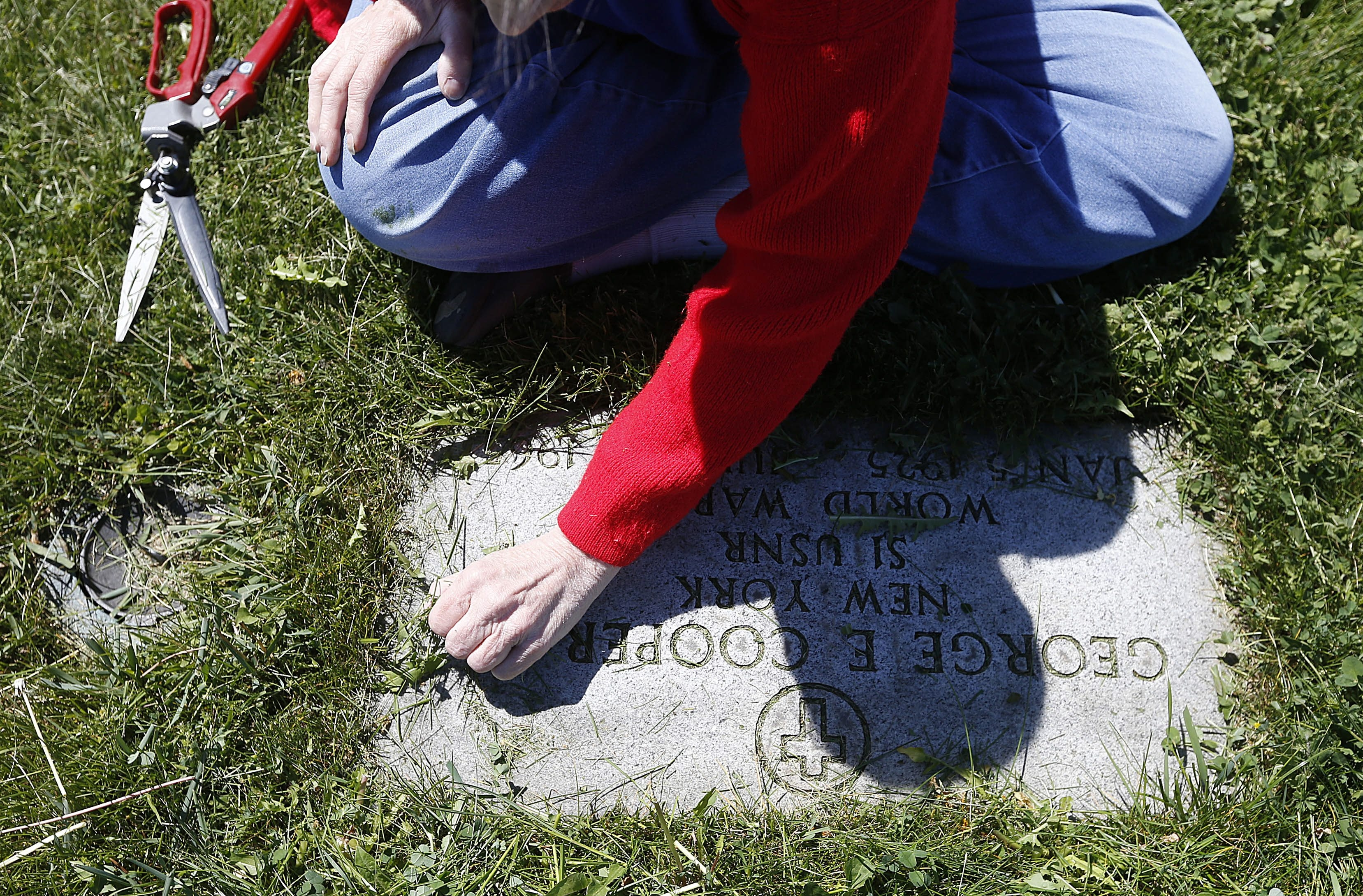 Lisa Cooper uses gardening scissors and a soft touch to trim back the grass on her father George E. Cooper Jr.'s gravestone at Mount Olivet Cemetery in the Town of Tonawanda.