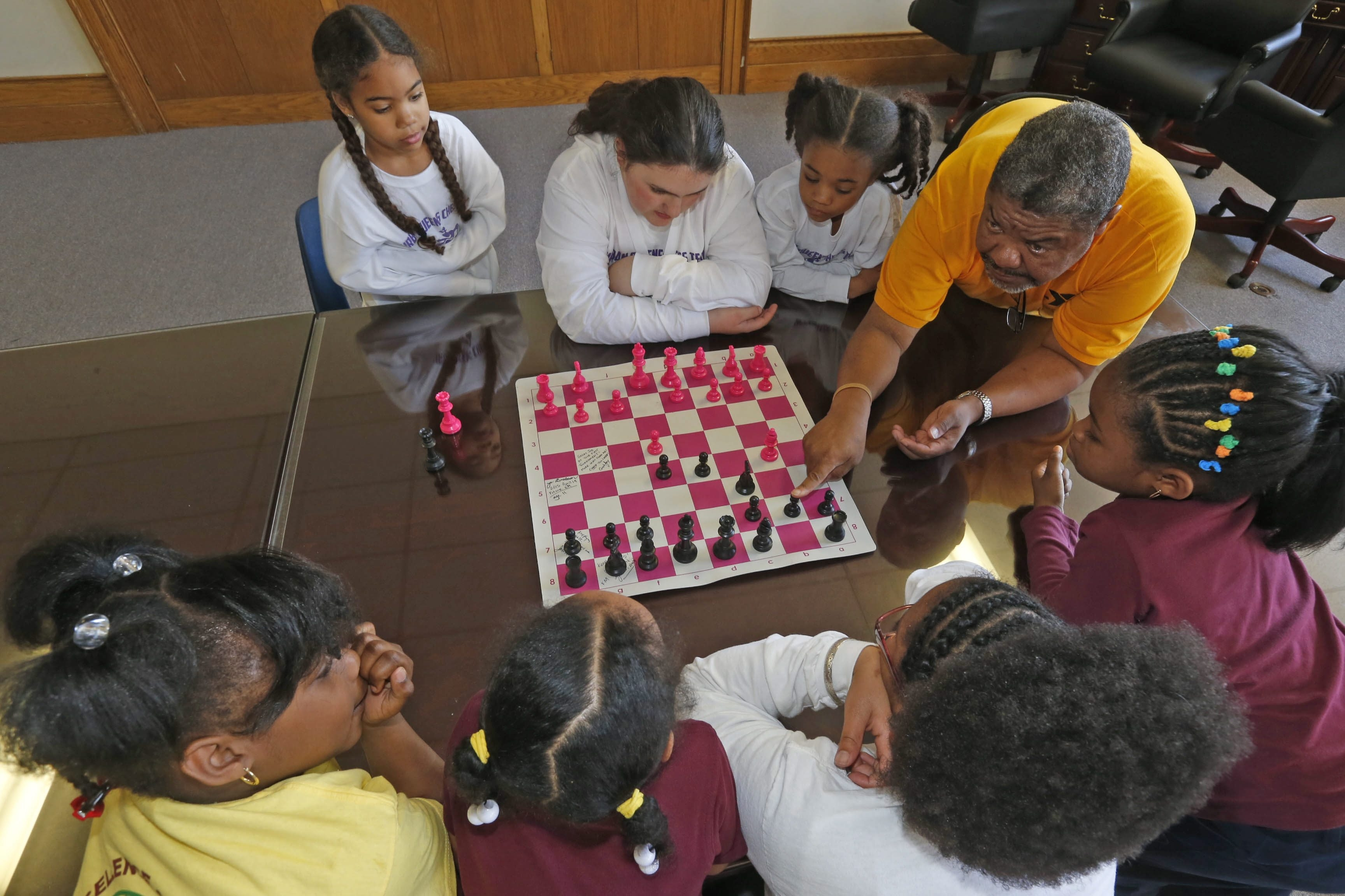Urban Queens Chess Team coach Michael A. McDuffie discusses chess moves with, clockwise from top, Victoria Albain, 7; Bryanna Ely, 13; Angelina Albain, 8; Ary'ana Griffa, 8; Antoinette Marshall, 10; Janiyah Ward, 7; and Rayven Jones, 8.