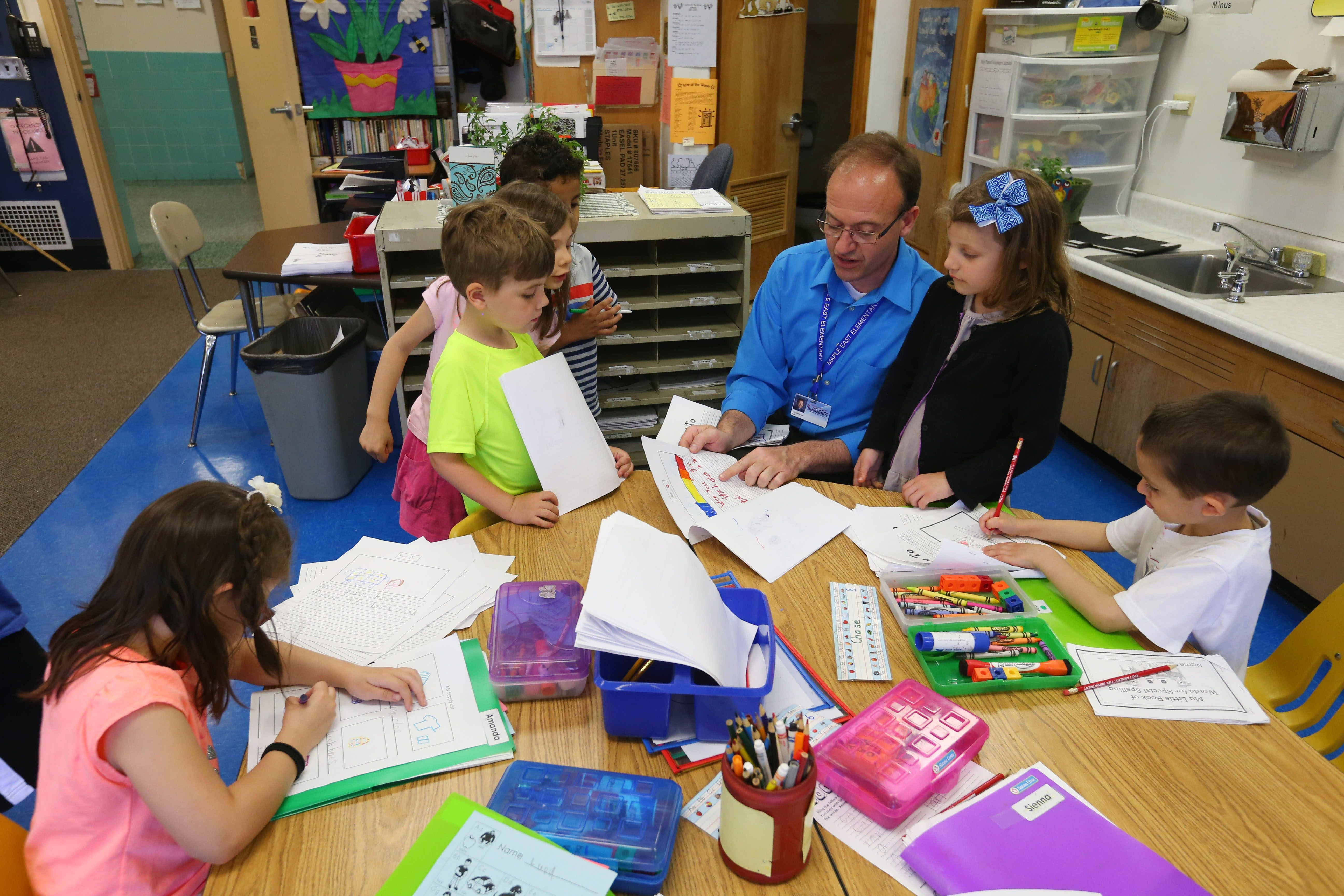 Kindergartners work on a project with teacher Alan Miller at Maple East Elementary in the Williamsville School District. (Mark Mulville/Buffalo News)