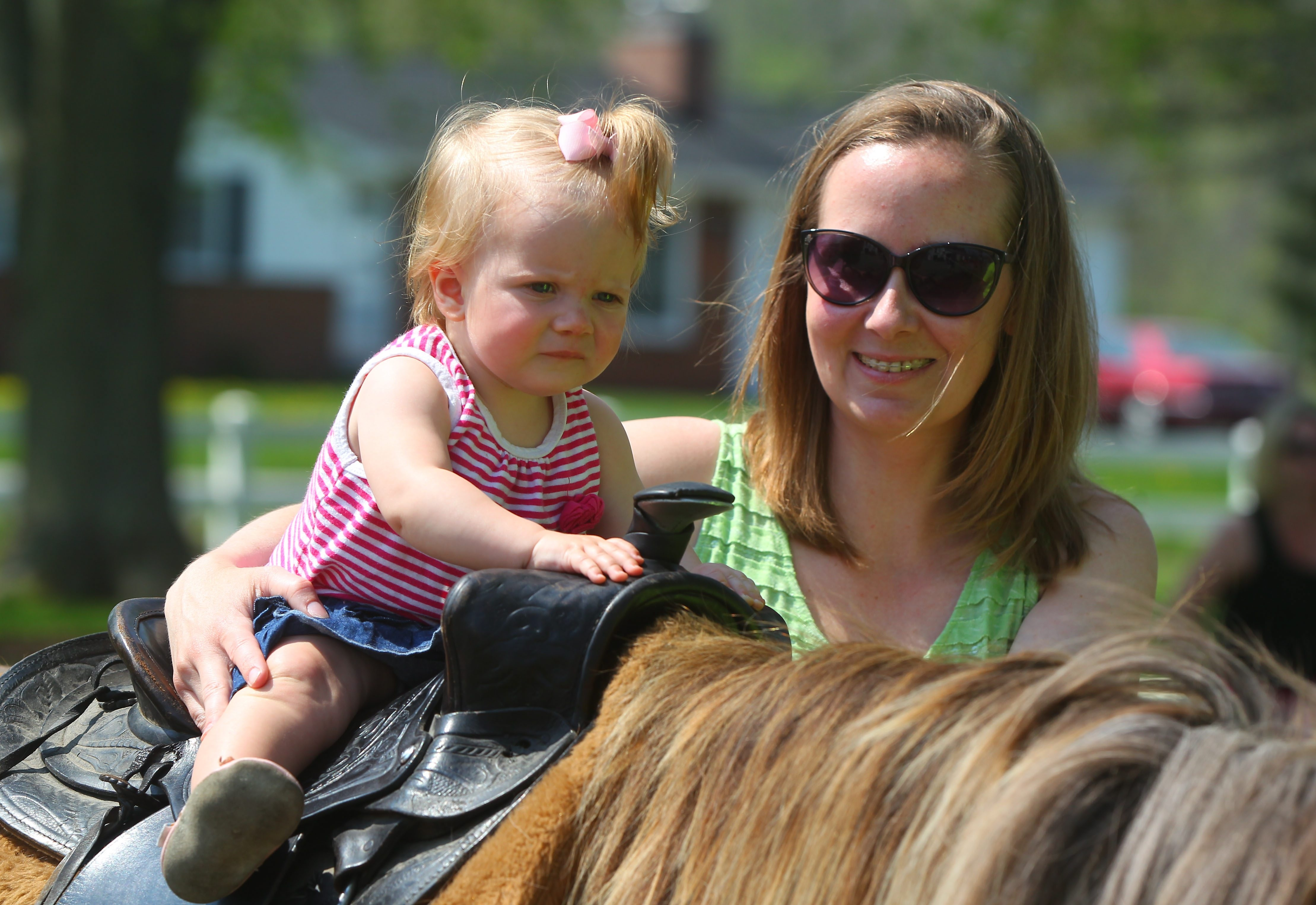 Ashley Bowersox holds her daughter Audra as she takes a pony ride during Mother's Day Down on the Farm at the Kelkenberg farm in Clarence on Sunday. See a photo gallery at buffalonews.com