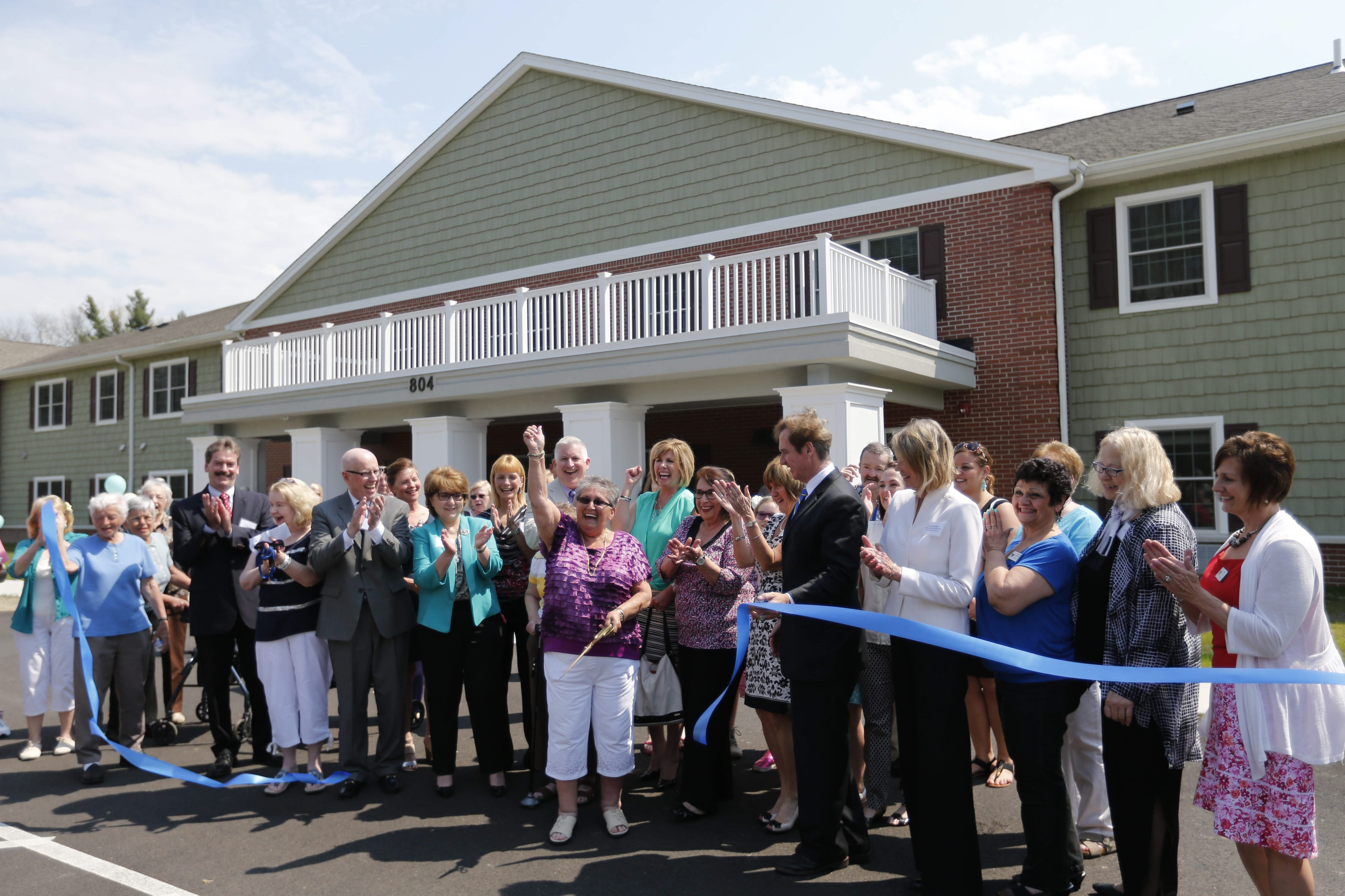 Resident Marilyn Donohue raises her arm after cutting the ribbon at the grand opening celebration for the residents of the Walnut Senior Living complex in West Seneca on Friday.