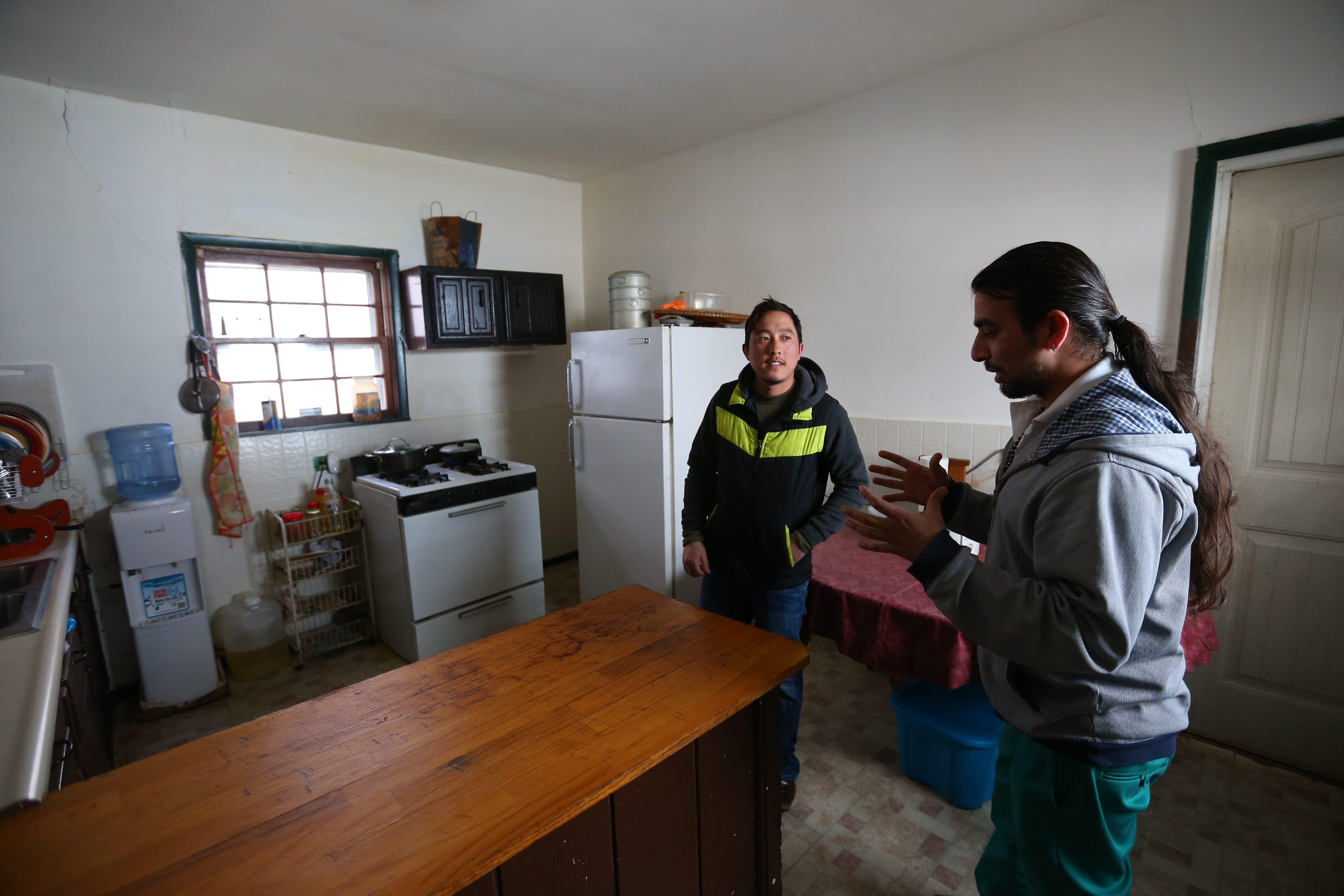 Jericho Road worker Govinda Subedi, right, points out potential home health hazards to Hem Magar.