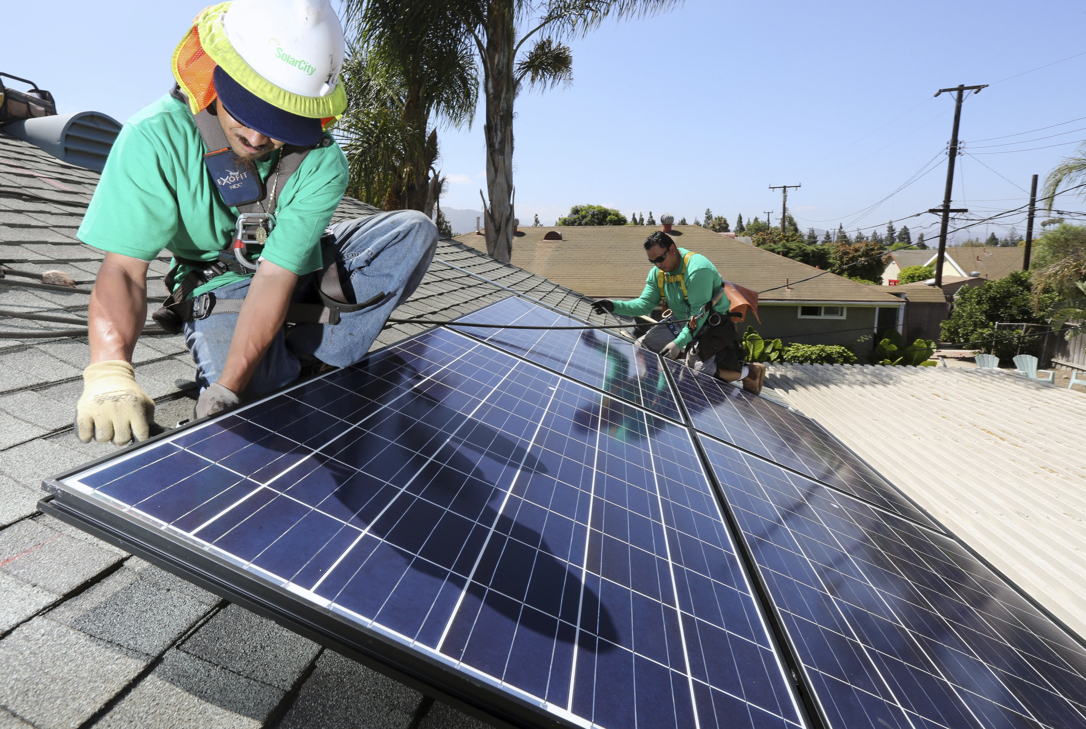 Workers from SolarCity install solar panels on a home in Camarillo, Calif.(New York Times)