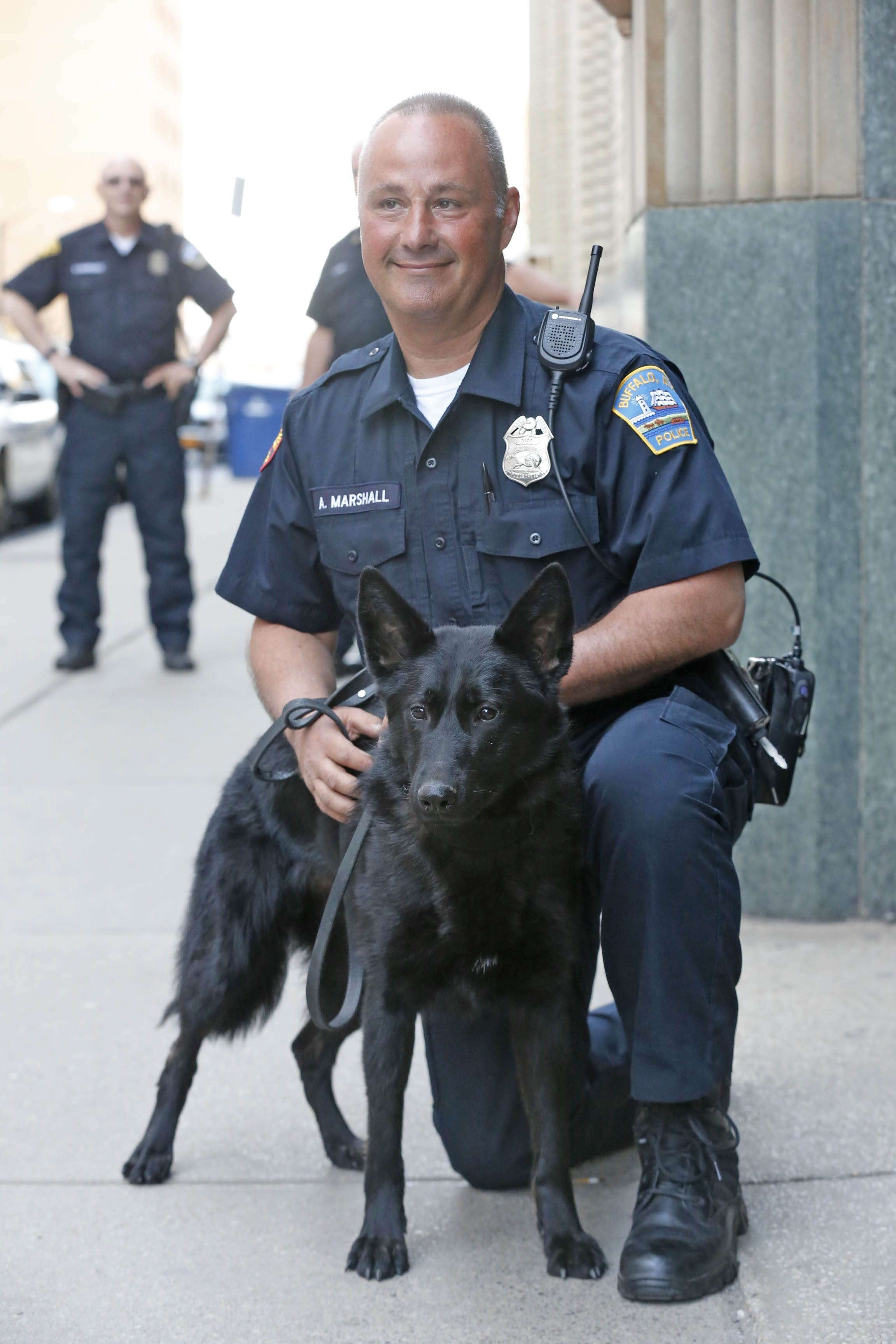 Officer Anthony Marshall introduces his new partner, Georgie, at Buffalo Police Department Headquarters on Monday. The Hyde family donated funding for the K-9 dog's training.