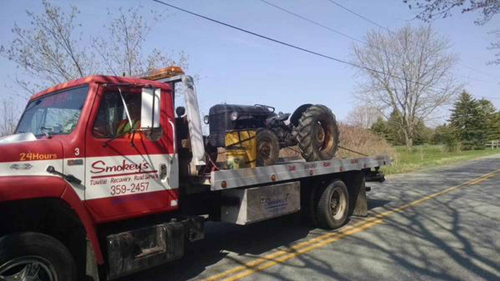 A flatbed truck hauls away the tractor and the pine tree from Sunday accident in Wales that took two lives. (Joseph Popiolkowski/Special to The News)