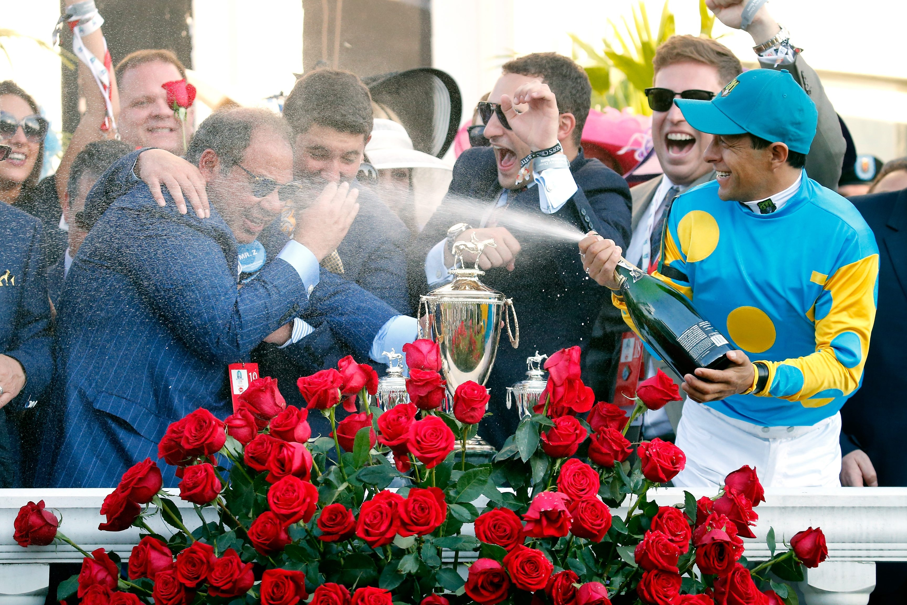 Jockey Victor Espinoza celebrates American Pharoah's Kentucky Derby win by spraying owner Ahmed Zayat with champagne in the winners' circle at Churchill Downs.