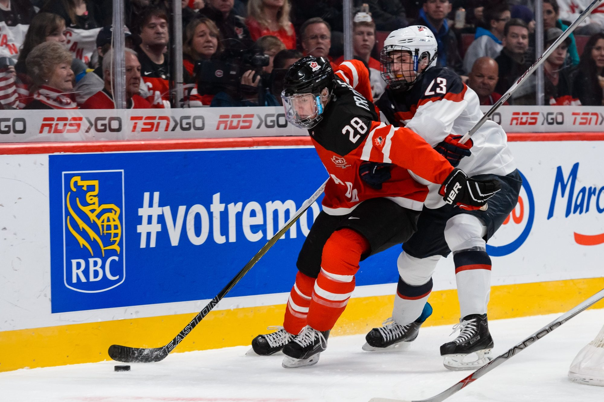 MONTREAL, QC - DECEMBER 31:  Zach Werenski #23 of Team United States challenges Lawson Crouse #28 of Team Canada near the boards during the 2015 IIHF World Junior Hockey Championship game at the Bell Centre on December 31, 2014 in Montreal, Quebec, Canada.  (Photo by Minas Panagiotakis/)