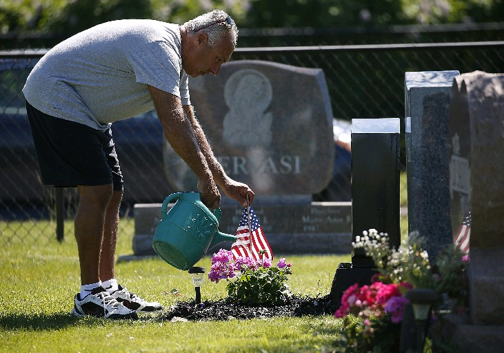 Bone dry top soil around Western New York made it tough to put American flags in the ground Memorial Day weekend. Charles D. Gramaglia of Clarence uses a watering can at the grave of his parents at Mount Olivet Cemetery in Kenmore. His father, Joseph A. Gramaglia, was a WWII Army veteran in Europe. (Robert Kirkham/Buffalo News)