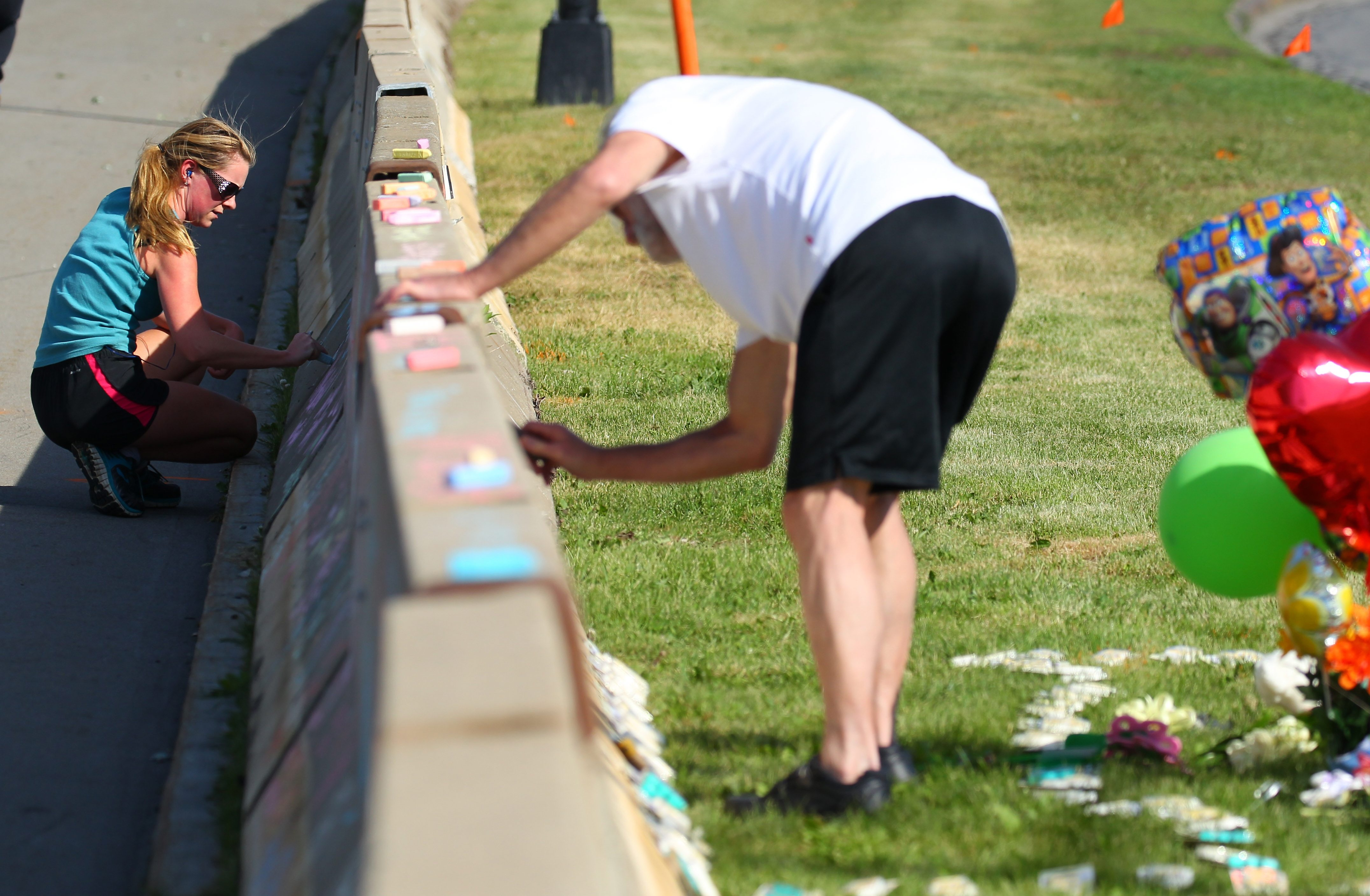 People write on the concrete barriers erected near the place where 3-year-old Maksym Sugorovskiy died in Delaware Park.