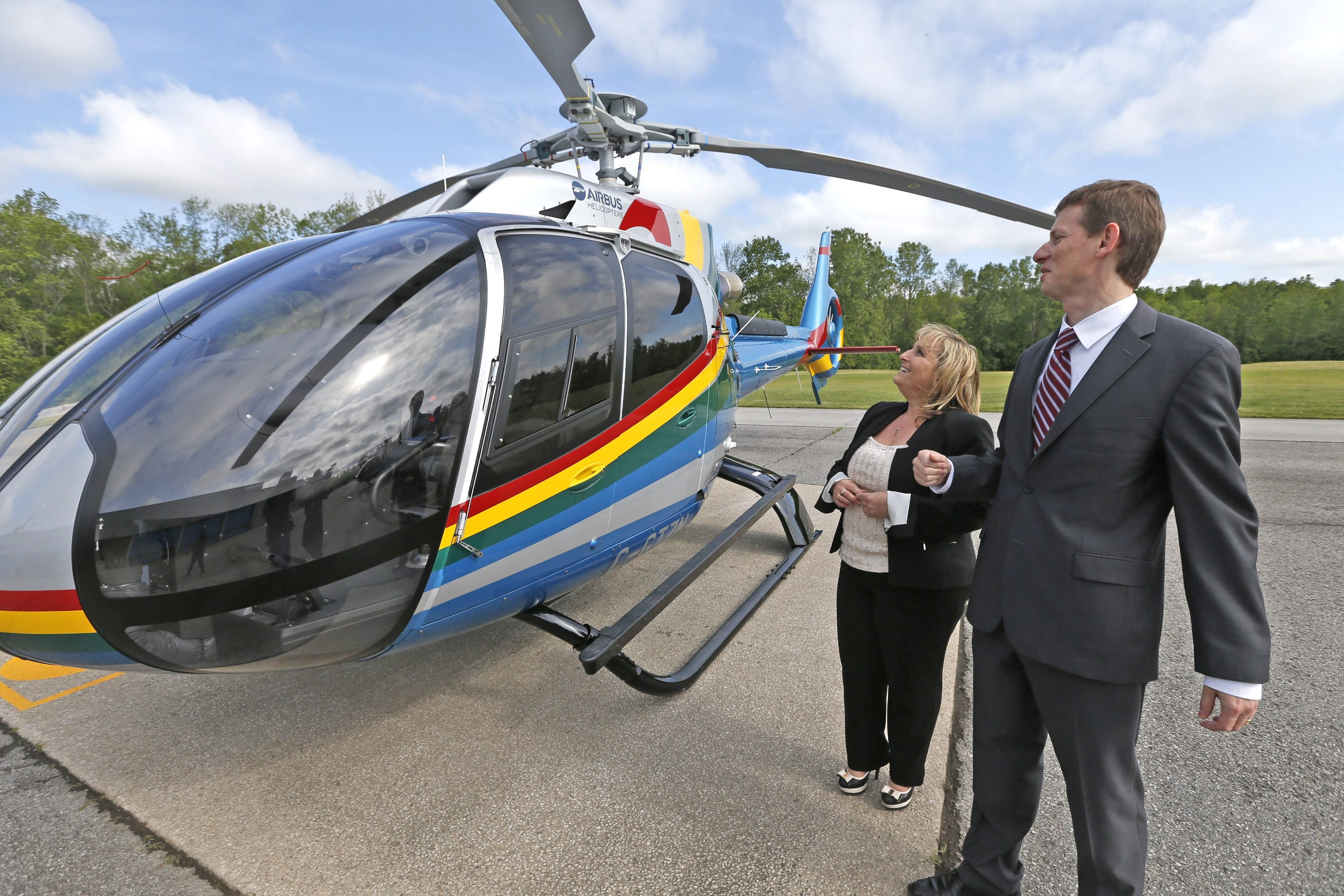 Romain Trapp, CEO of Airbus Helicopters Canada, and Anna Pierce, vice president of Niagara Helicopters Ltd., admire one of the four H130s that the Fort Erie, Ont., manufacturer sold to the company, which provides aerial tours of Niagara Falls.