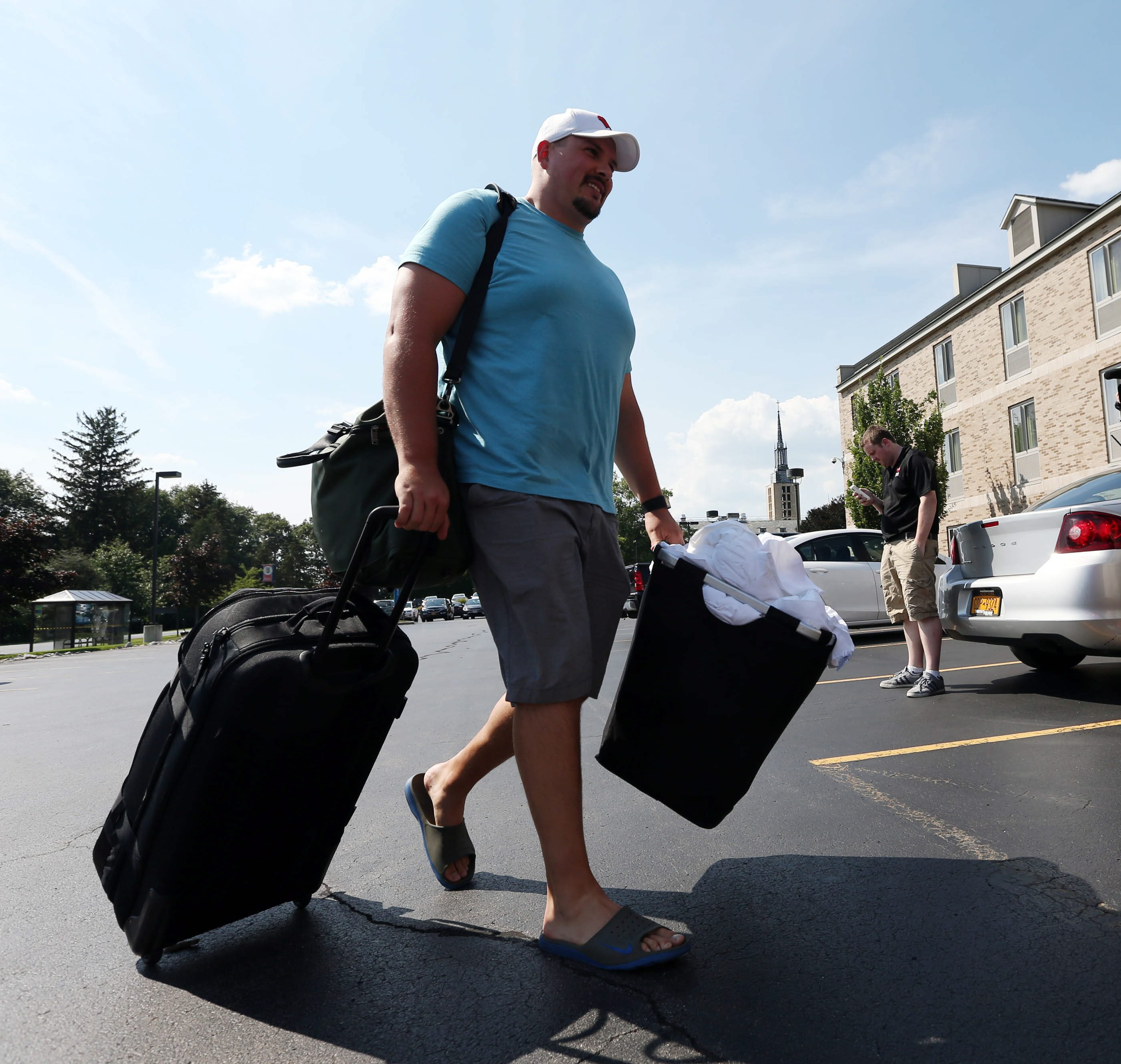 Guard Kraig Urbik, an early arrival, hauls some of his belongings to the Bills' team dorm at St. John Fisher College on Wednesday.