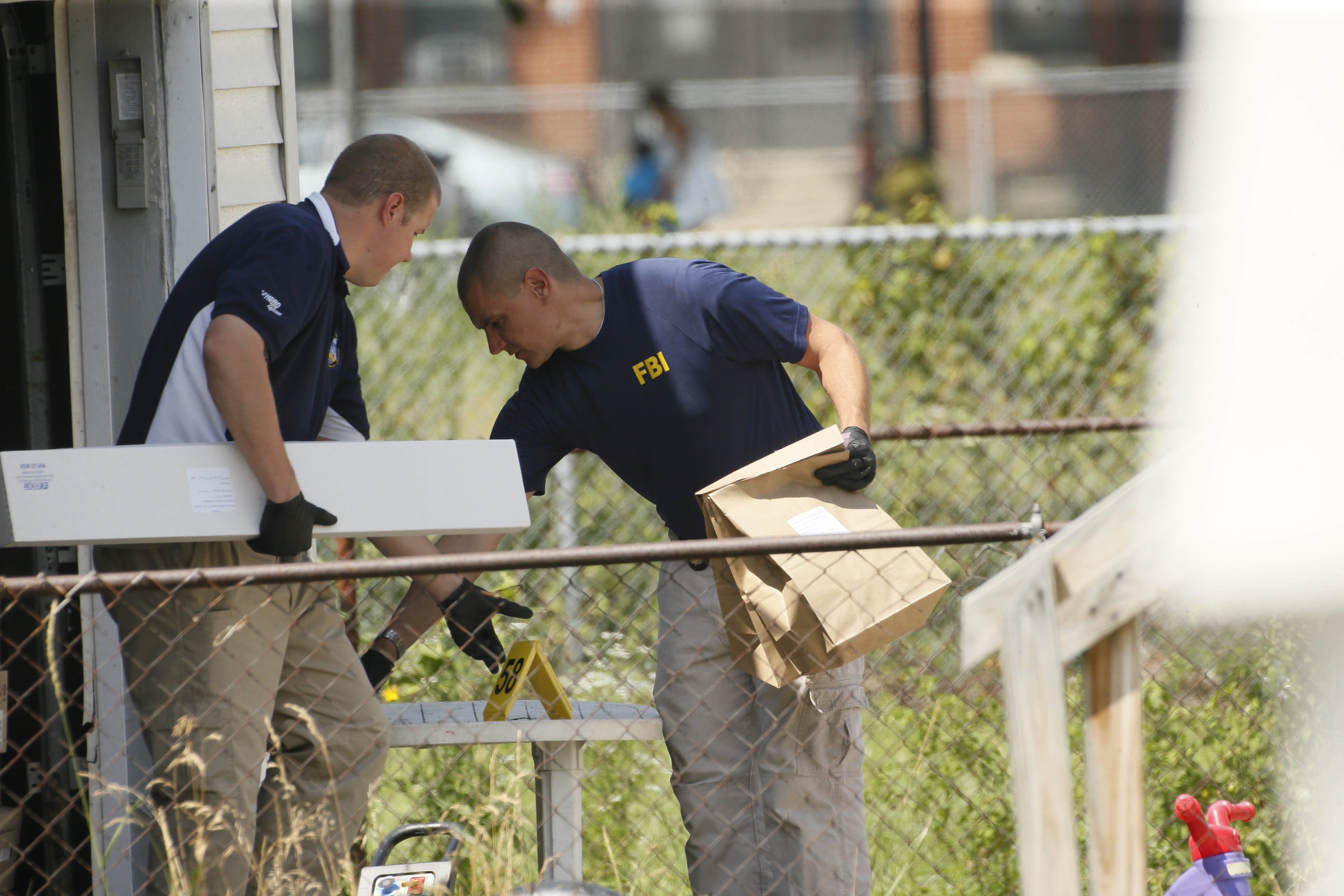 FBI evidence technicians carry materials from the garage at the Lackawanna home of Arafat M. Nagi.