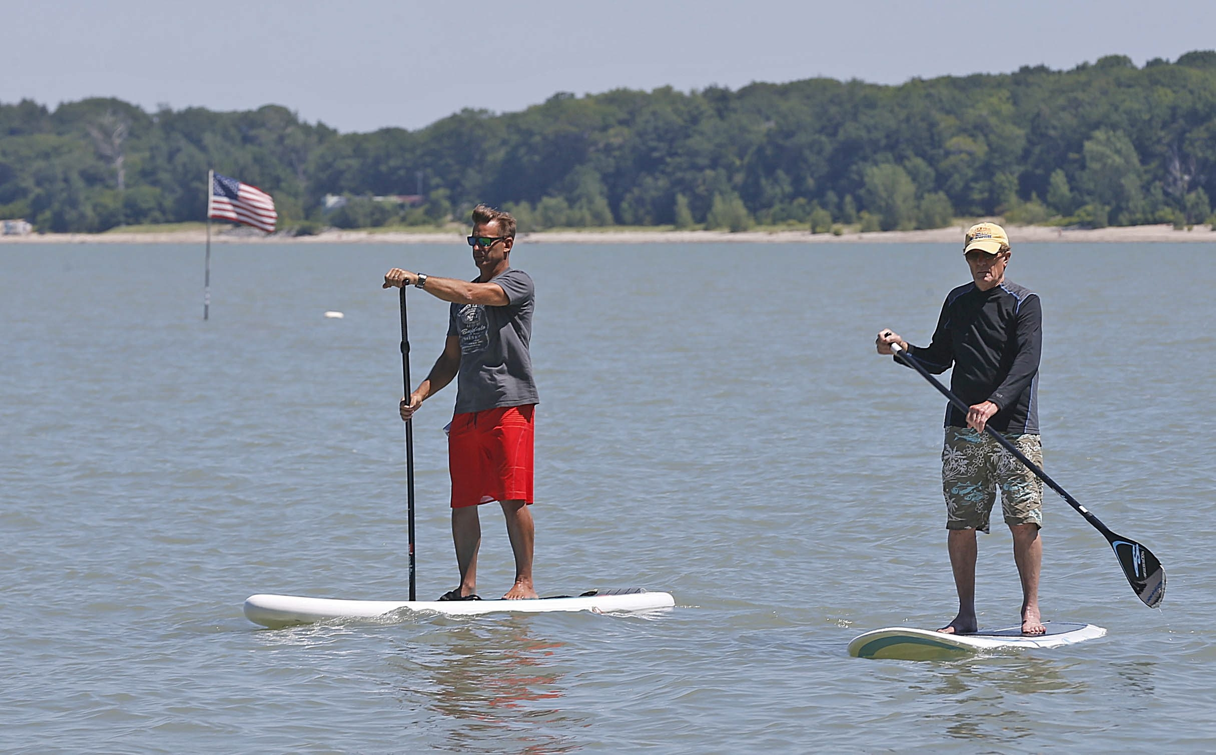 Ward Pinkel, left, and Ben Little, two Grandview Bay residents, paddle around near a U.S. flag in the water near their cottages. Pinkel placed the flag there several years ago to warn boaters of shallow waters – not recently a problem thanks to heavy rain – and rocks.