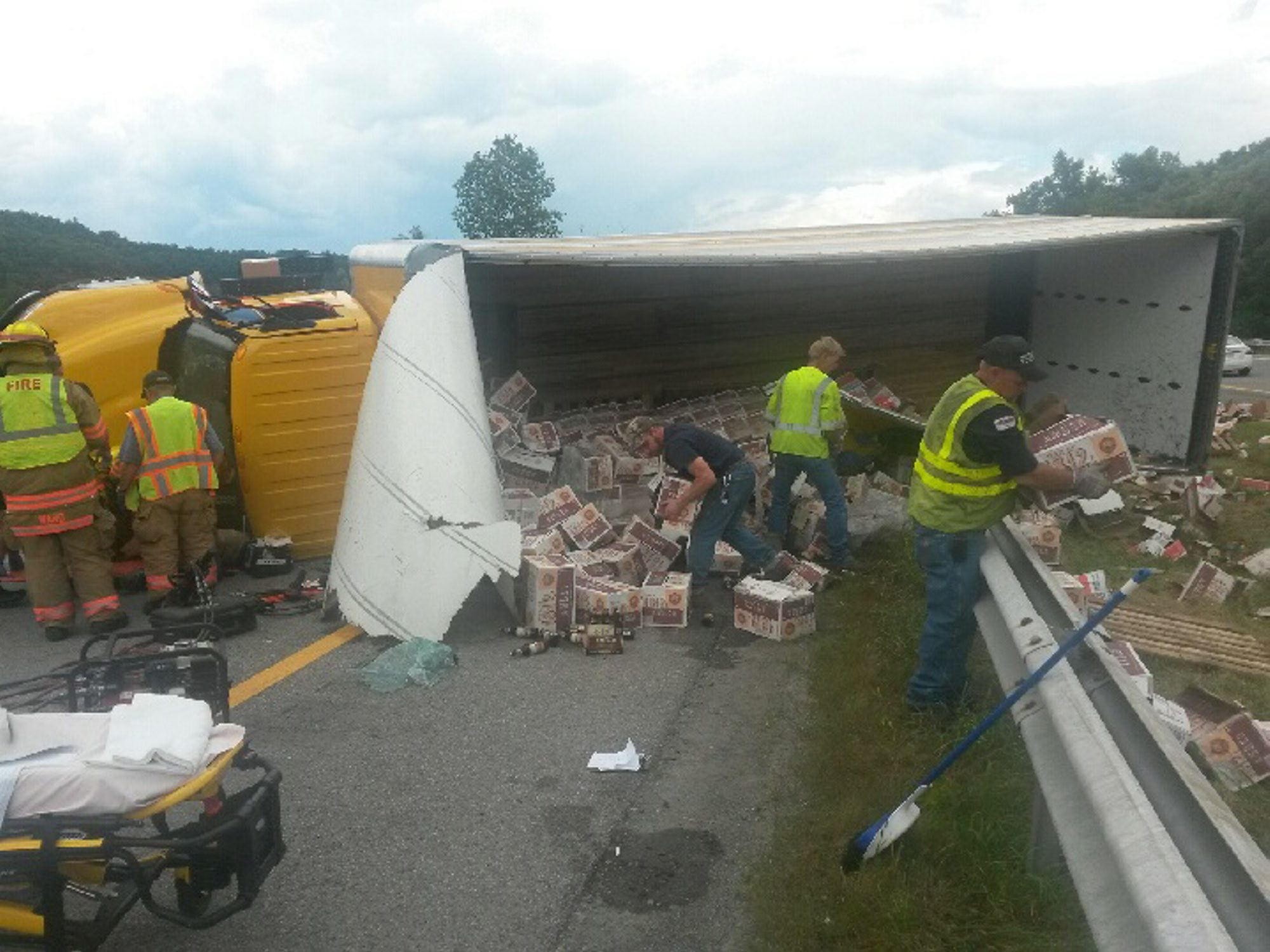 Emergency responders clean up the scene of a tractor-trailer rollover on the Thruway past Utica on Friday afternoon.