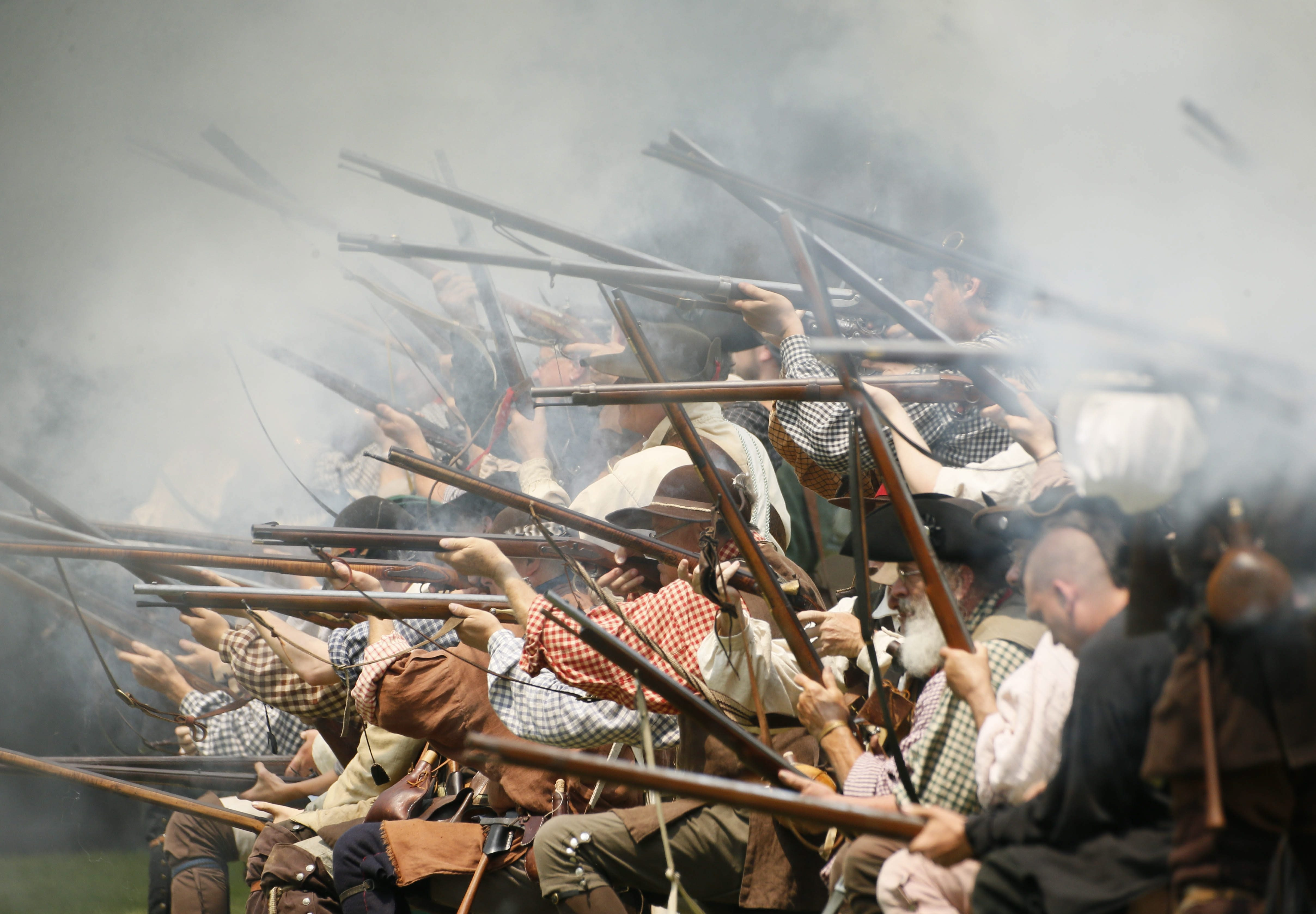 A line of infantrymen fire their muskets as re-enactors portray the British attack on the French at Old Fort Niagara during the French and Indian War Encampment on July 5.
