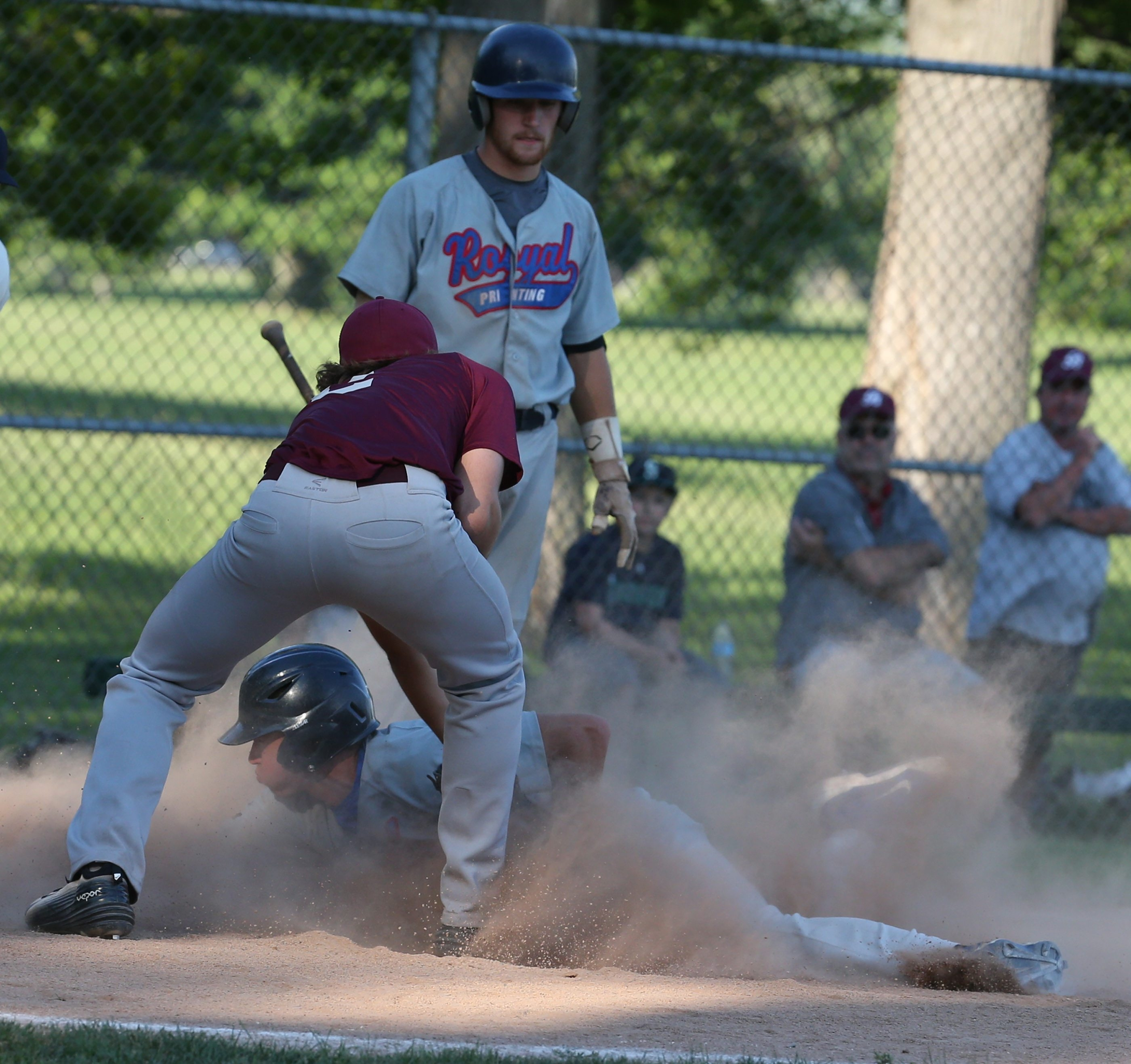 Royal Printing's  Ken Johnson arrives at the plate in a cloud of dust as he scores in the second inning of the local All-American Amateur Baseball Association semifinal at Delaware Park Thursday.