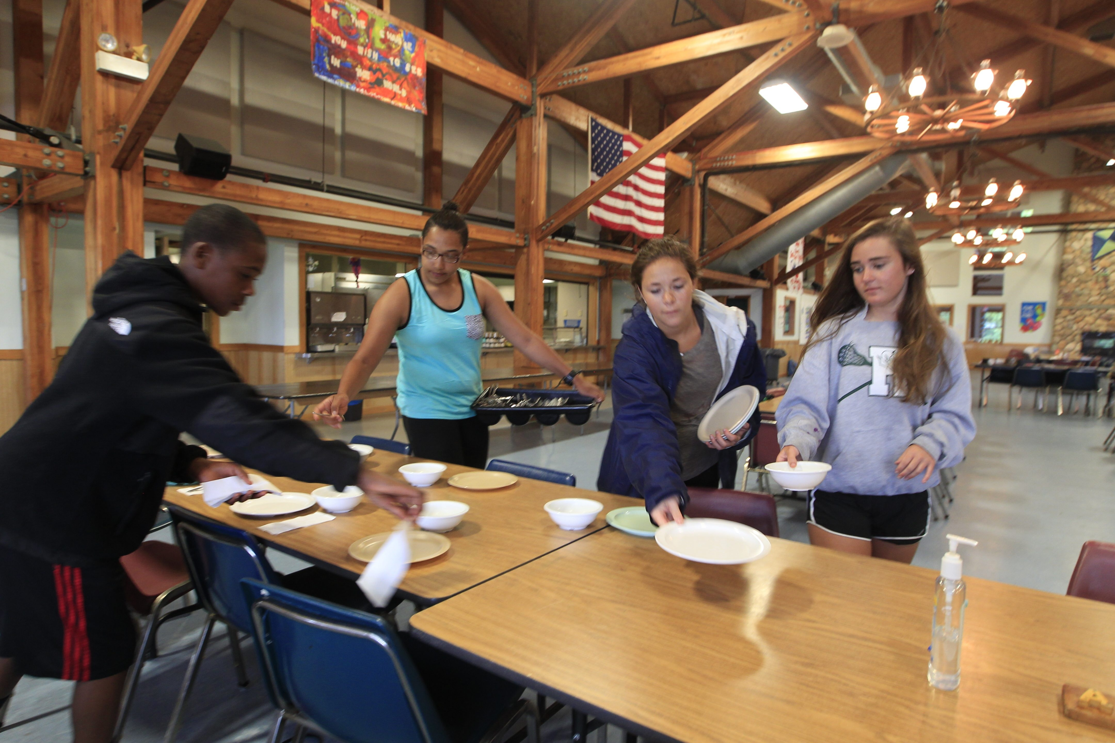 Cradle Beach counselors Destiny Kennedy, 19, second from left, Abby Adams, 17, and Emma Inslinger, 17, right, help camper Jalen Carter-Keith, 14, set a table in the camp's dining hall last week in Angola.