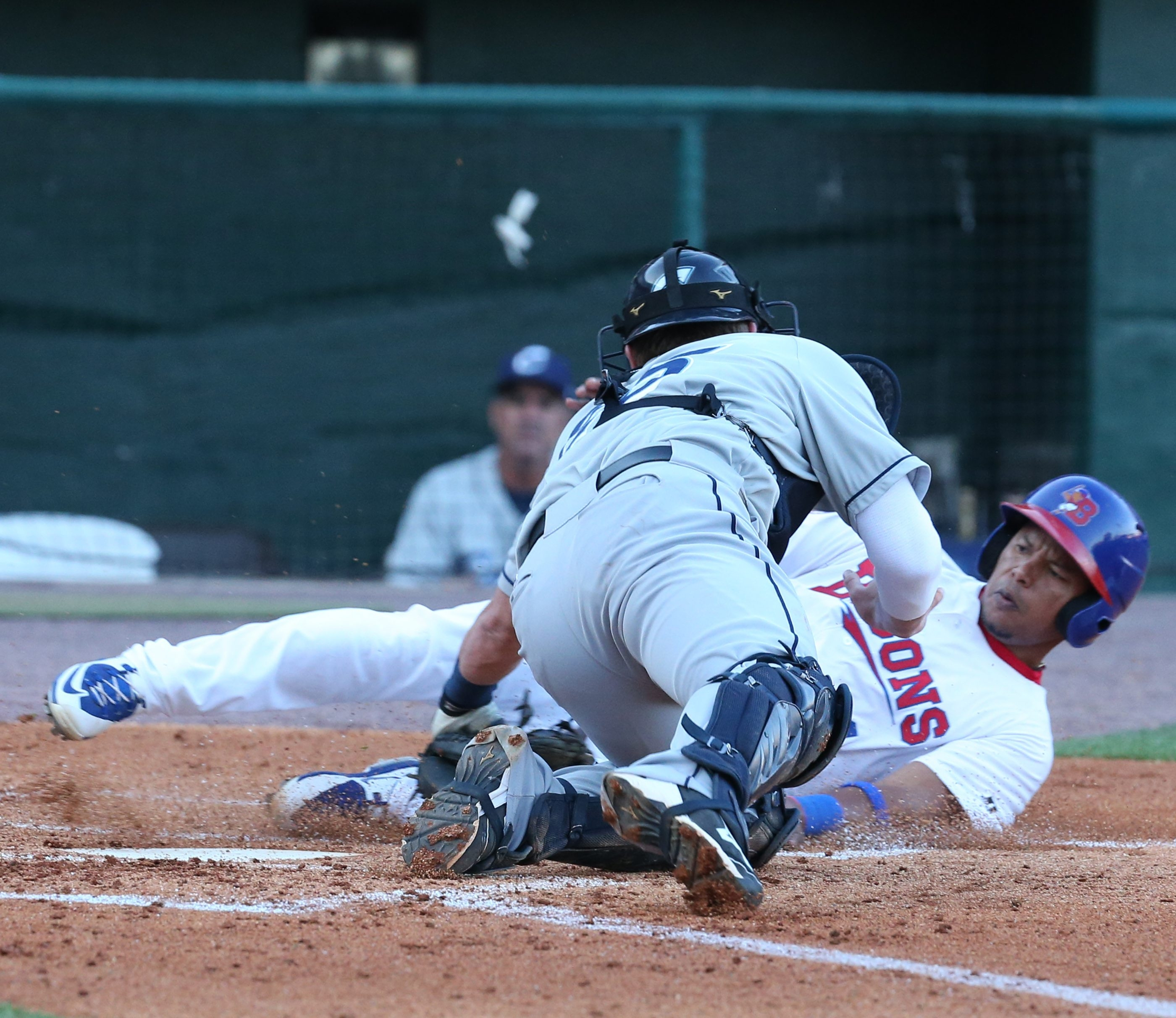 Buffalo's Ramon Santiago is tagged out by Columbus catcher Adam Moore at home plate in the second inning of Thursday's game.