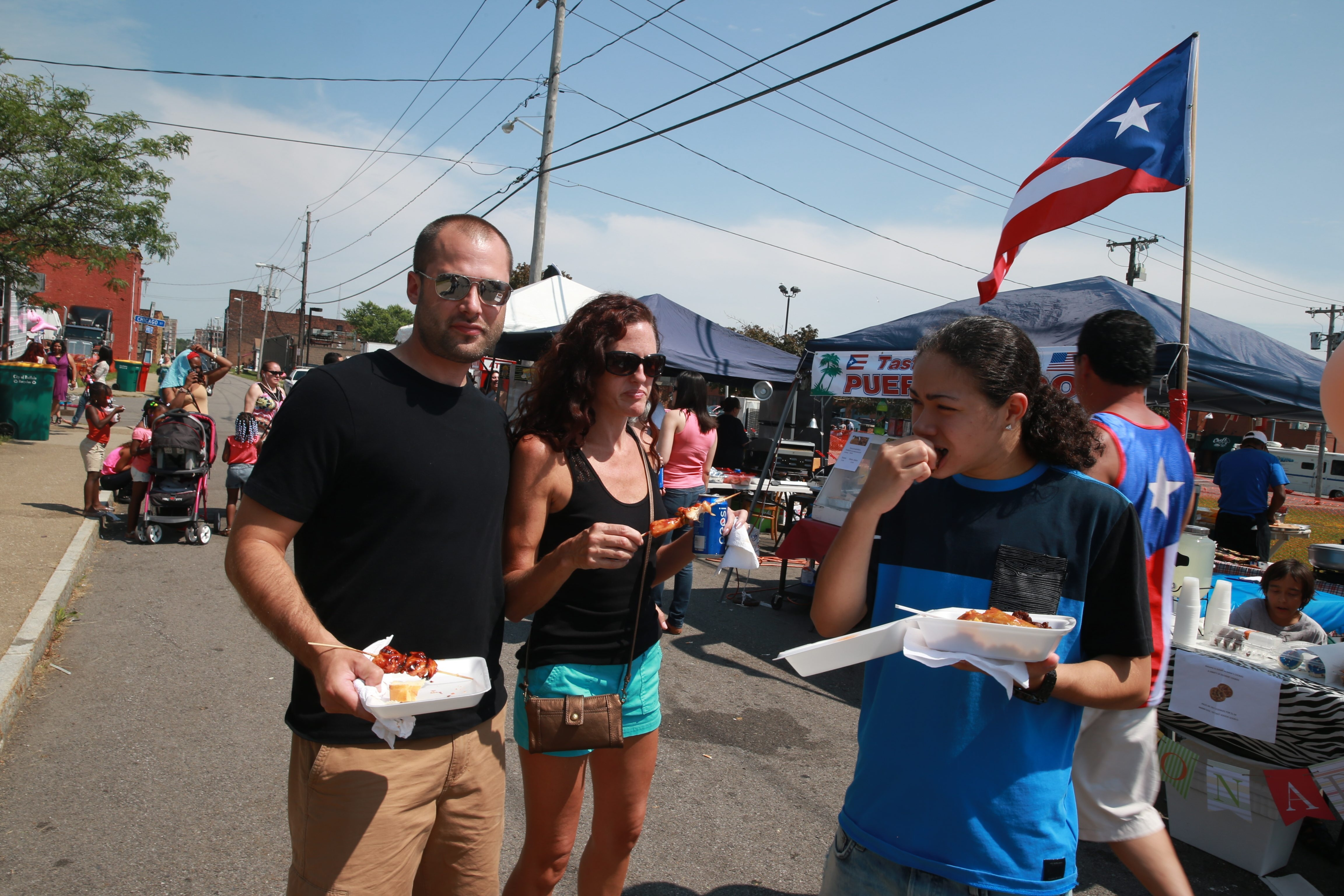 Scott Wheeler, left, his fiancée, Allison Hibbs, middle, and their niece Indalis Santiago of Depew munch on some food at the Grease Pole Festival, a three-day event that celebrates Puerto Rican and Hispanic hertitage. See more photos from the festival at buffalonews.com/galleries.